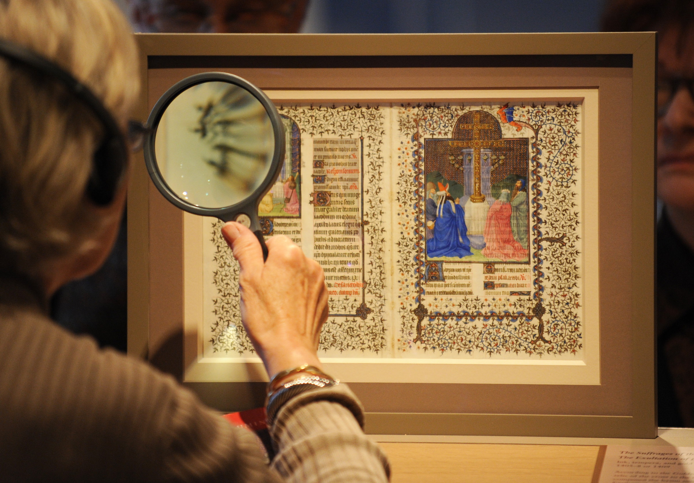 A woman uses a magnifying glass to view pages from a medieval prayer book known as the Belles Heures, on in 2010 at the Metropolitan Museum of Art in New York City.