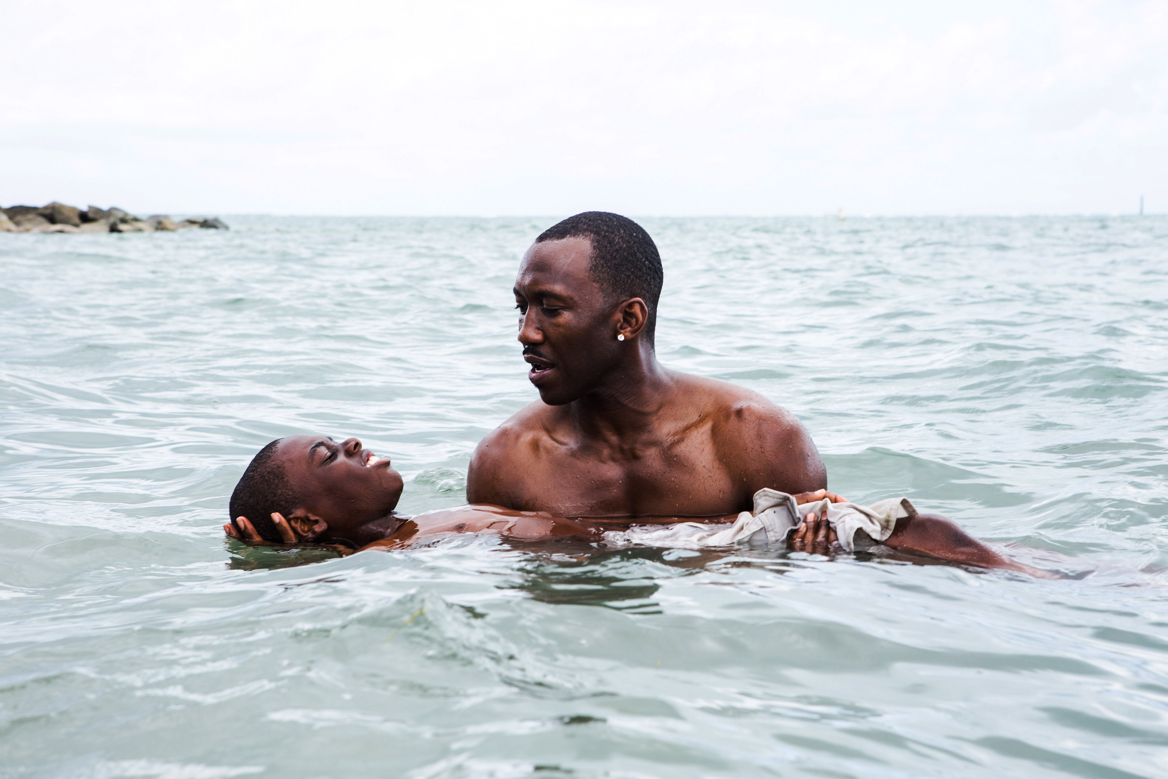 Mahershala Ali, holding Alex R. Hibbert, in Moonlight.