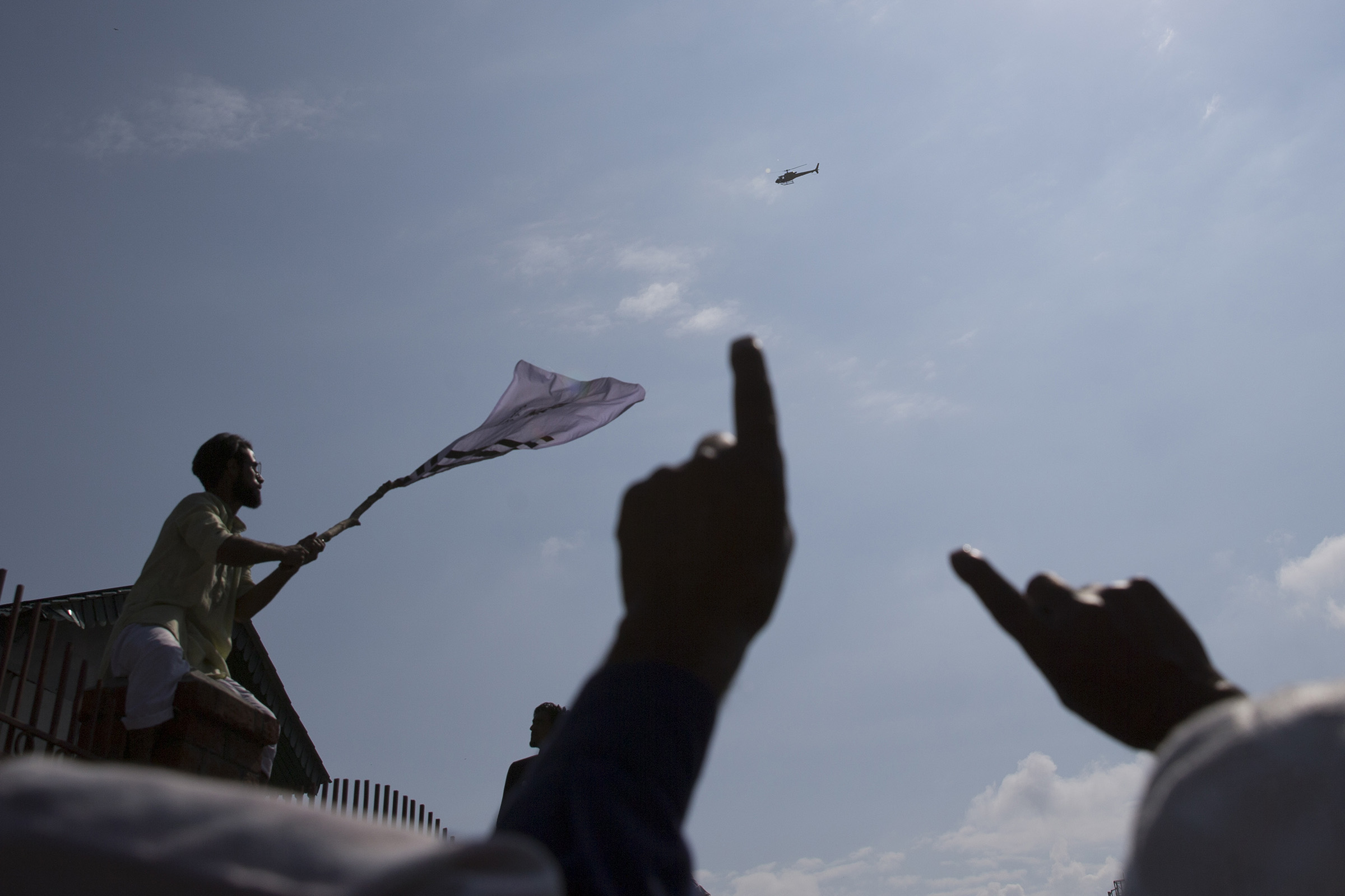 A Kashmiri protester waves a flag as Indian authorities in a helicopter monitor a protest after Eid prayers in Srinagar, Indian controlled Kashmir, on Aug. 12, 2019.