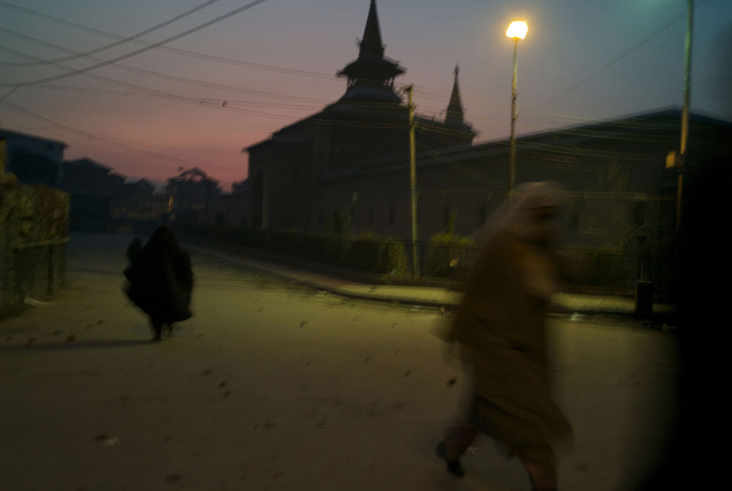Women make their way home at dusk as clouds of tear gas engulfs the air in the stone strewn streets surrounding the Jama Masjed following riots in Srinagar in Dec. 2008.