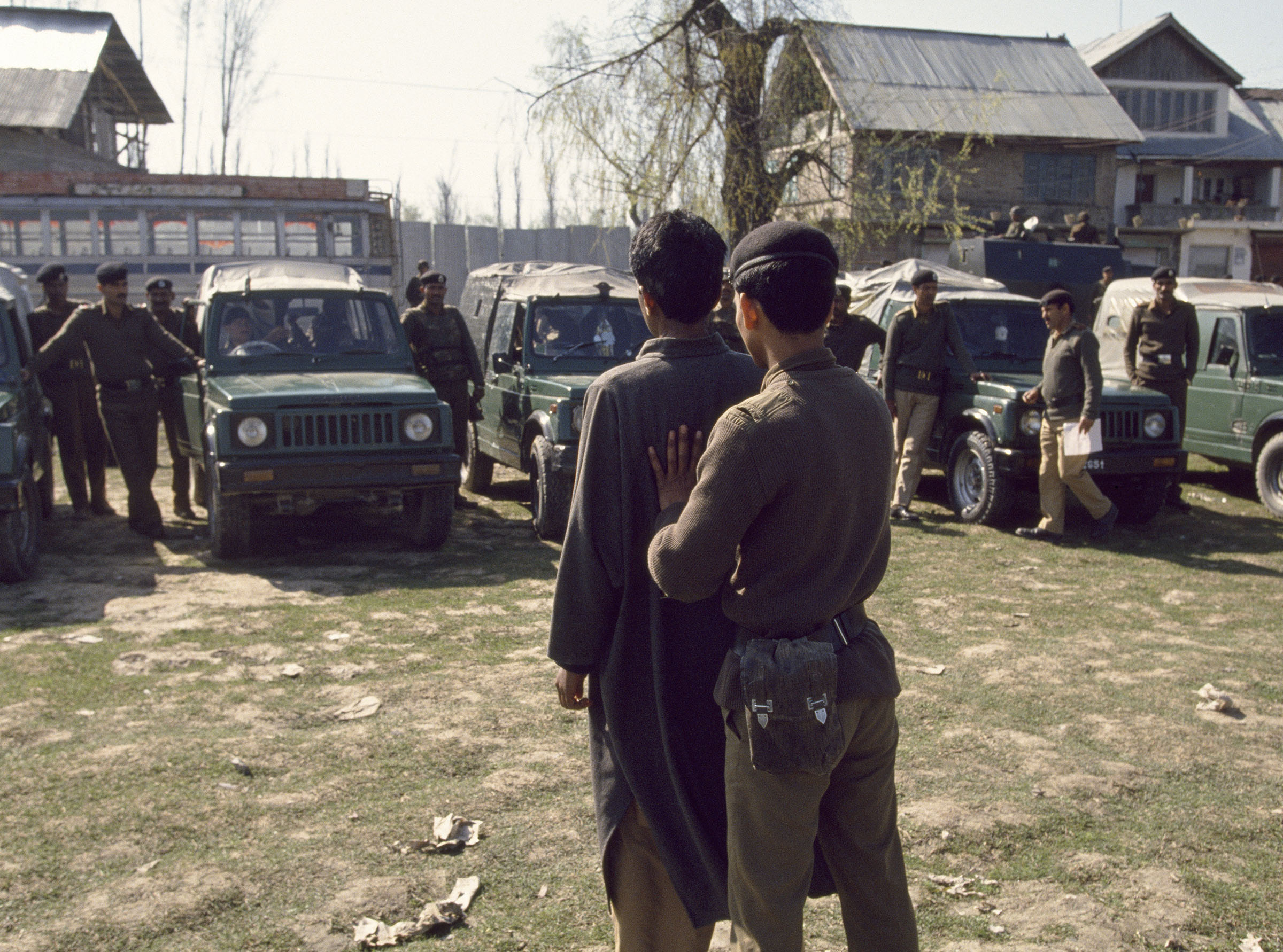 An Indian Border Security Force soldier shows a suspected militant to people in a line of parked military vehicles, Srinagar, India, on July 28, 1994.