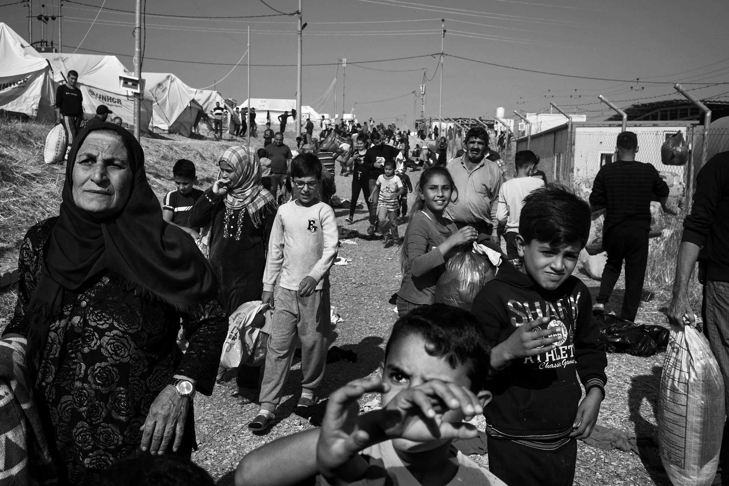 Syrian Kurdish refugees gather to receive winter clothes during a distribution inside the Bardarash camp on Oct. 31.