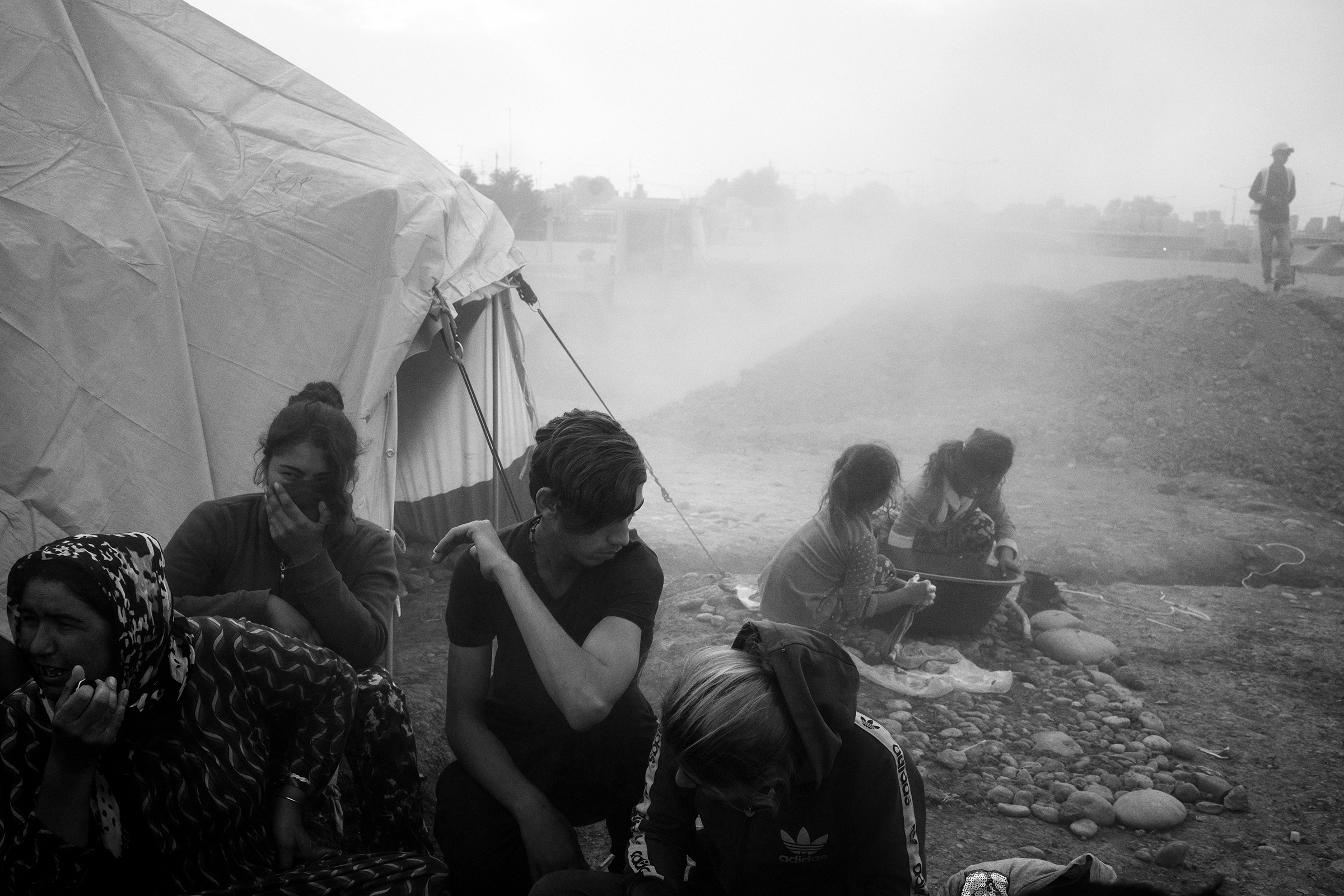 A newly arrived refugee family huddles together as dust from ongoing construction lingers in the air at the Gawilan camp in early November.