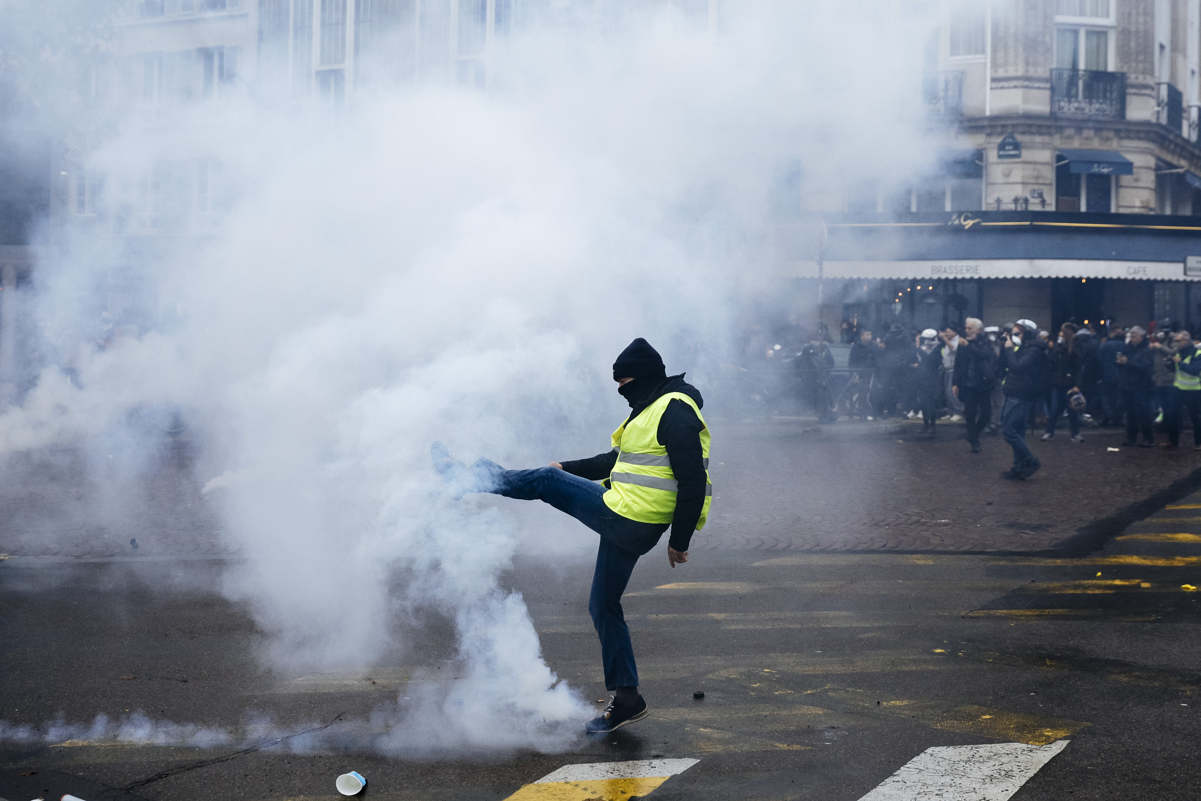 A protestor kicks away a tear gas canister during a yellow vest demonstration marking the first anniversary in Paris, Saturday, Nov. 16, 2019.