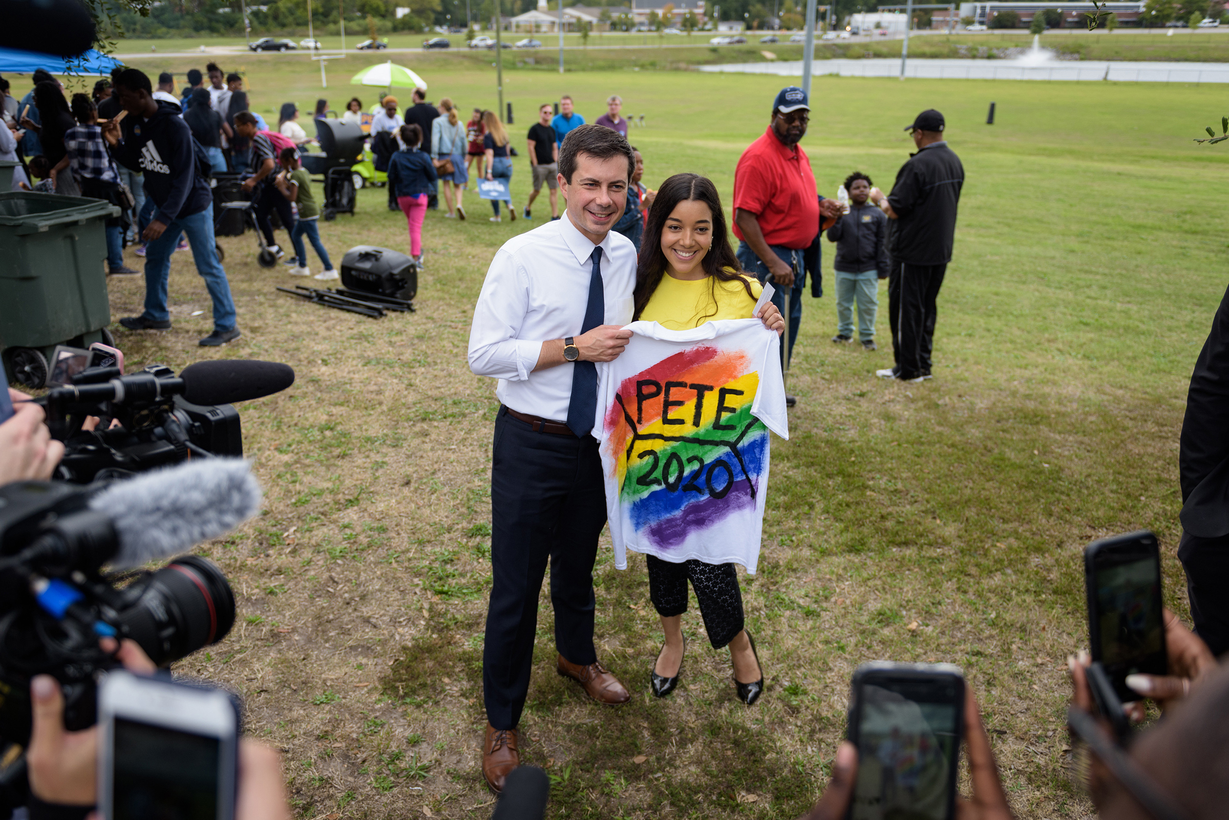 Mayor Pete Buttigieg of South Bend, Ind. poses for a photo with Kashmir Imani, holding a T-shirt she designed, during a homecoming tailgate event at Allen University, a historically black campus in Columbia, S.C., on Oct. 26, 2019.