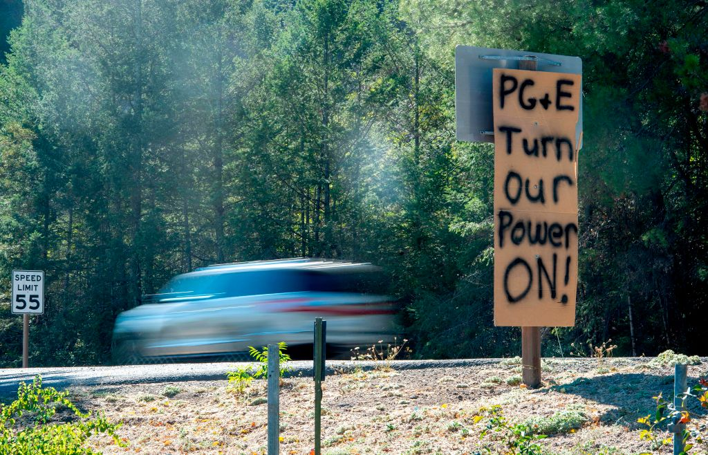 A sign calling for utility company PG&E to turn the power back on is seen on the side of the road during a statewide blackout in Calistoga, California, on October, 10, 2019.