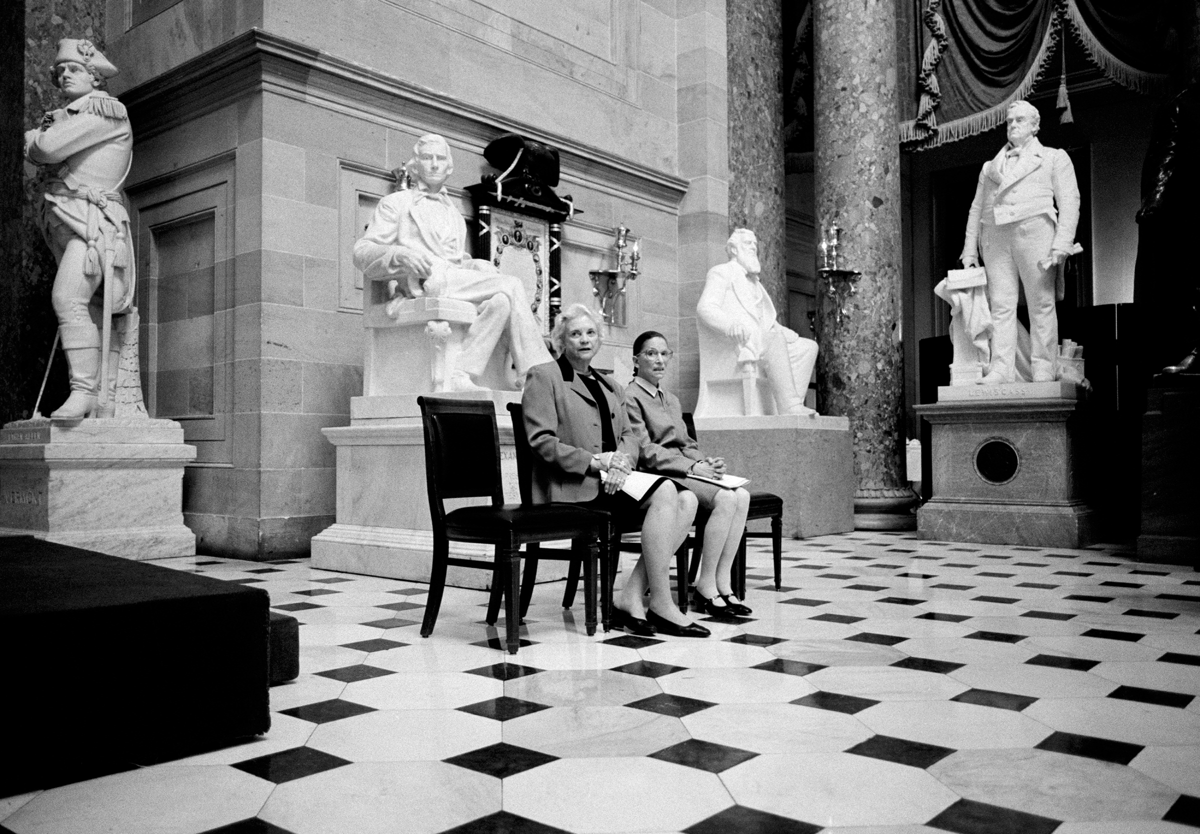 March 2001 The only two female Justices of the U.S. Supreme Court, Sandra Day O'Connor and Ruth Bader Ginsburg, pose for a portrait in Statuary Hall, surrounded by statues of men at the U.S. Capitol Building in Washington, D.C. The two Justices were preparing to address a meeting of the Congressional Women's Caucus.