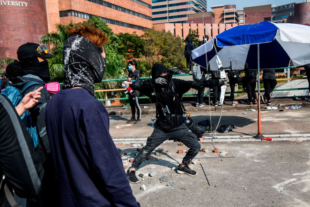 A protester unleashes an arrow while standing on a barricaded street outside The Hong Kong Polytechnic University on Nov. 15, 2019.