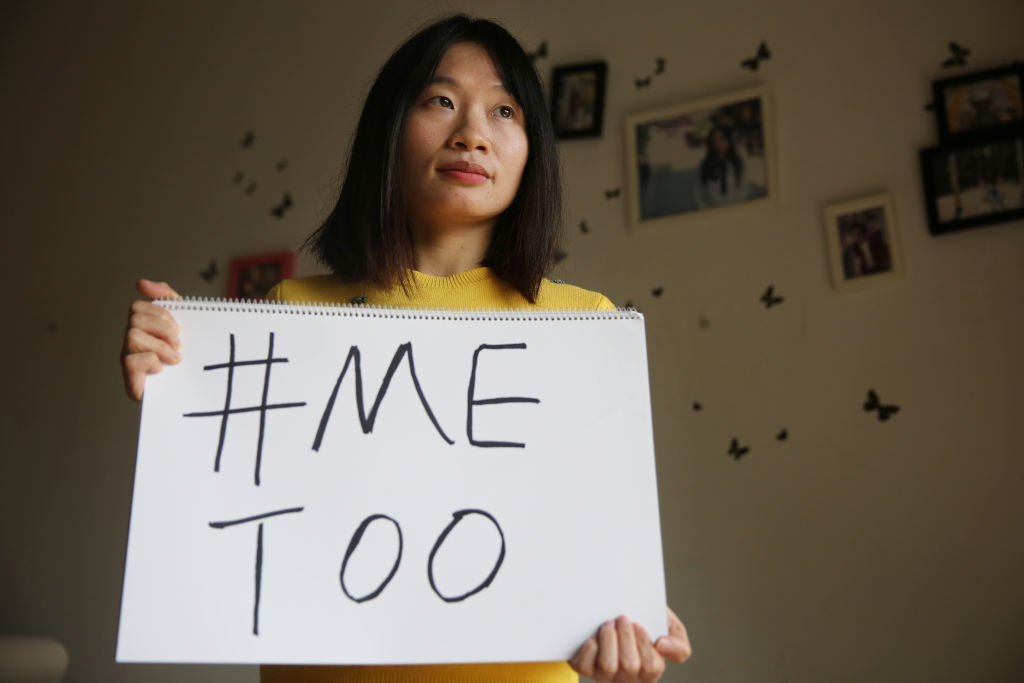 Sophia Huang Xueqin, a freelance journalist who was a key figure in the #MeToo movement in China, holds a sign at her home on Dec. 8, 2017.