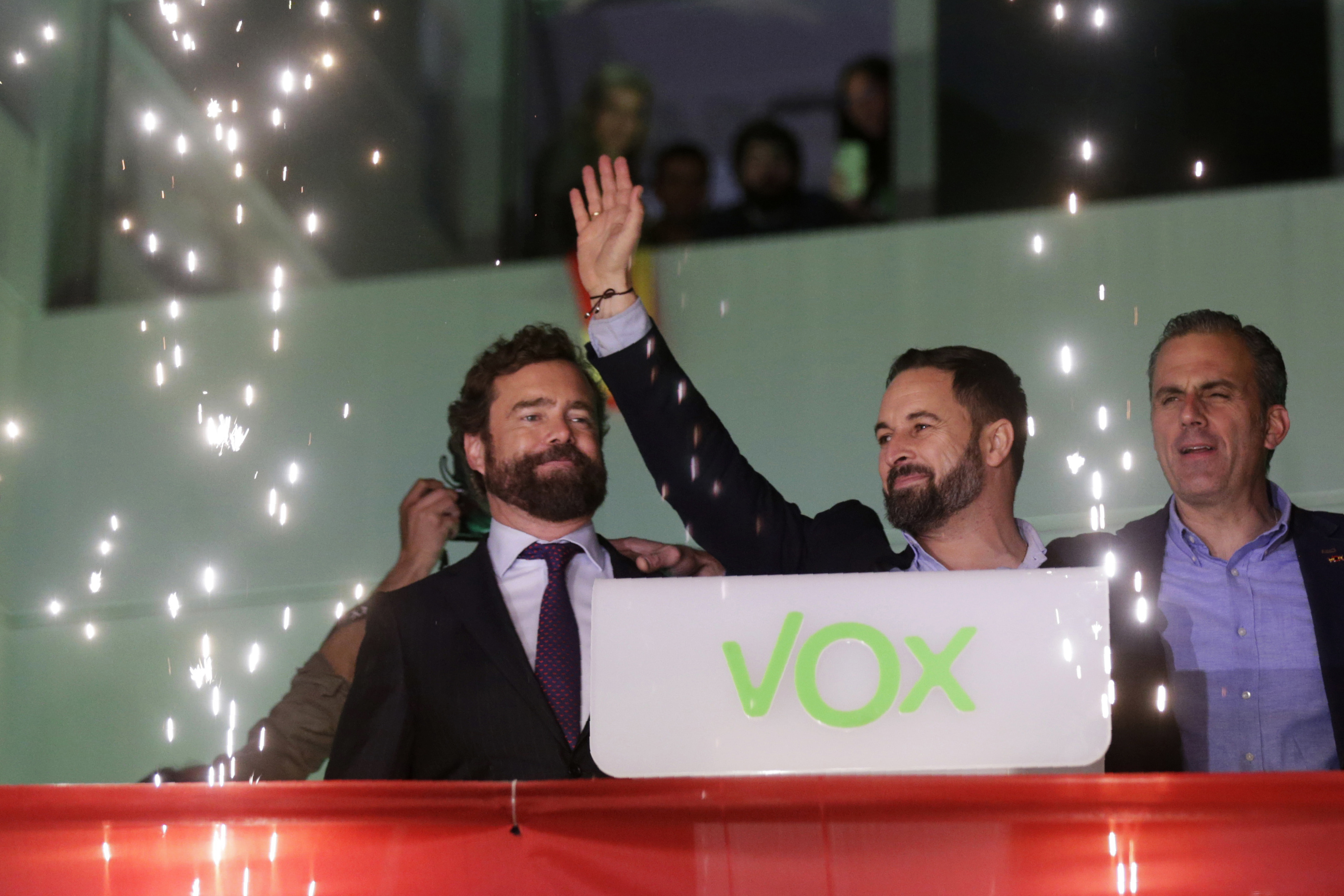 Santiago Abascal, leader of far-right Vox Party, waves to supporters as fireworks go off outside the party headquarters after the announcement of the general election first results, in Madrid on Nov. 10, 2019.