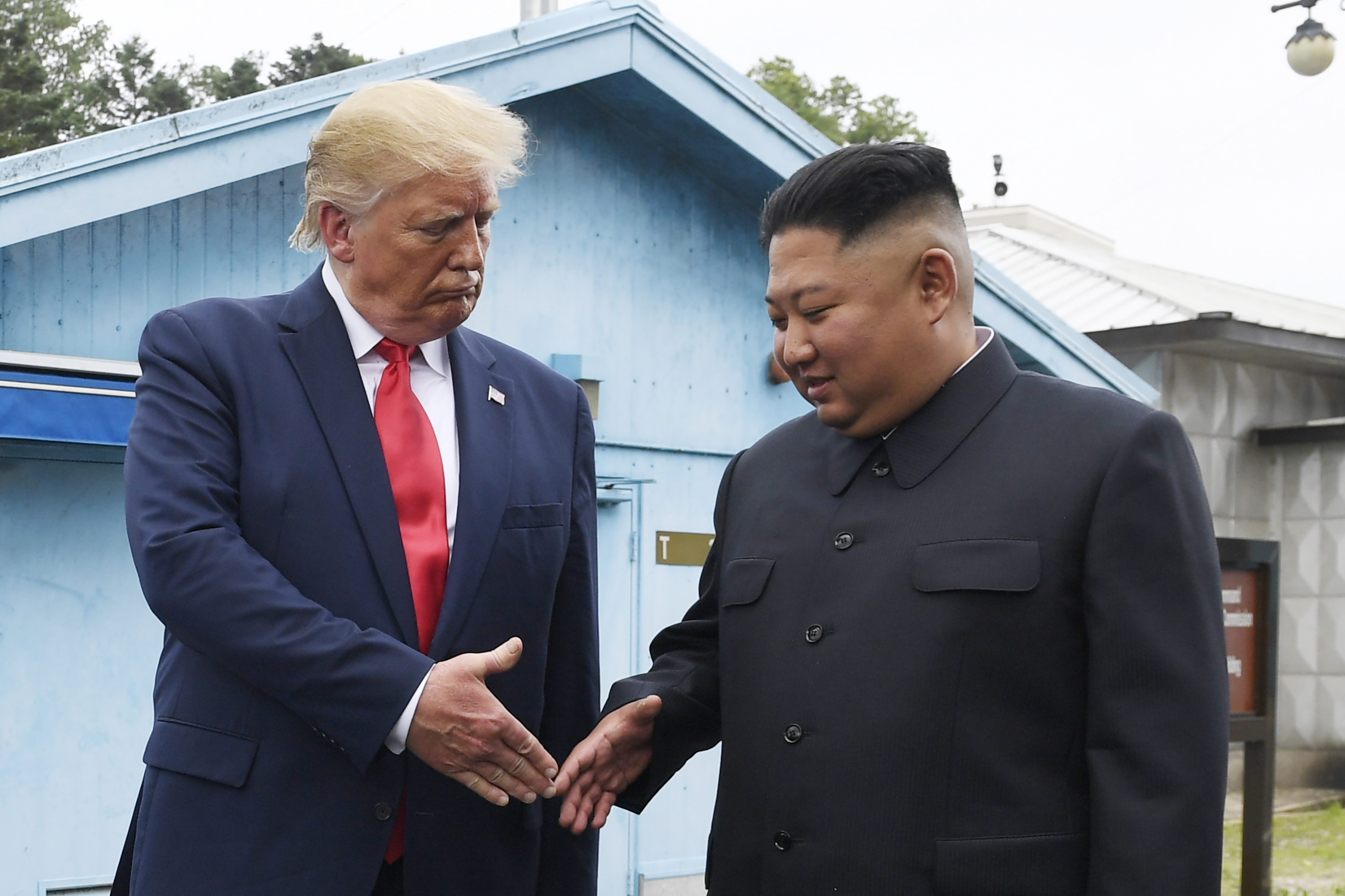 """In this June 30, 2019, file photo, North Korean leader Kim Jong Un, right, and U.S. President Donald Trump prepare to shake hands at the border village of Panmunjom in the Demilitarized Zone, South Korea. On Wednesday, Nov. 13, 2019, North Korea's supreme decision-making institution has lashed out at planned U.S.-South Korean drills and warned that the United States will face """"bigger threat and harsh suffering"""" if it ignores North Korean leader Kim Jong Un's end-of-year deadline to salvage the nuclear diplomacy."""