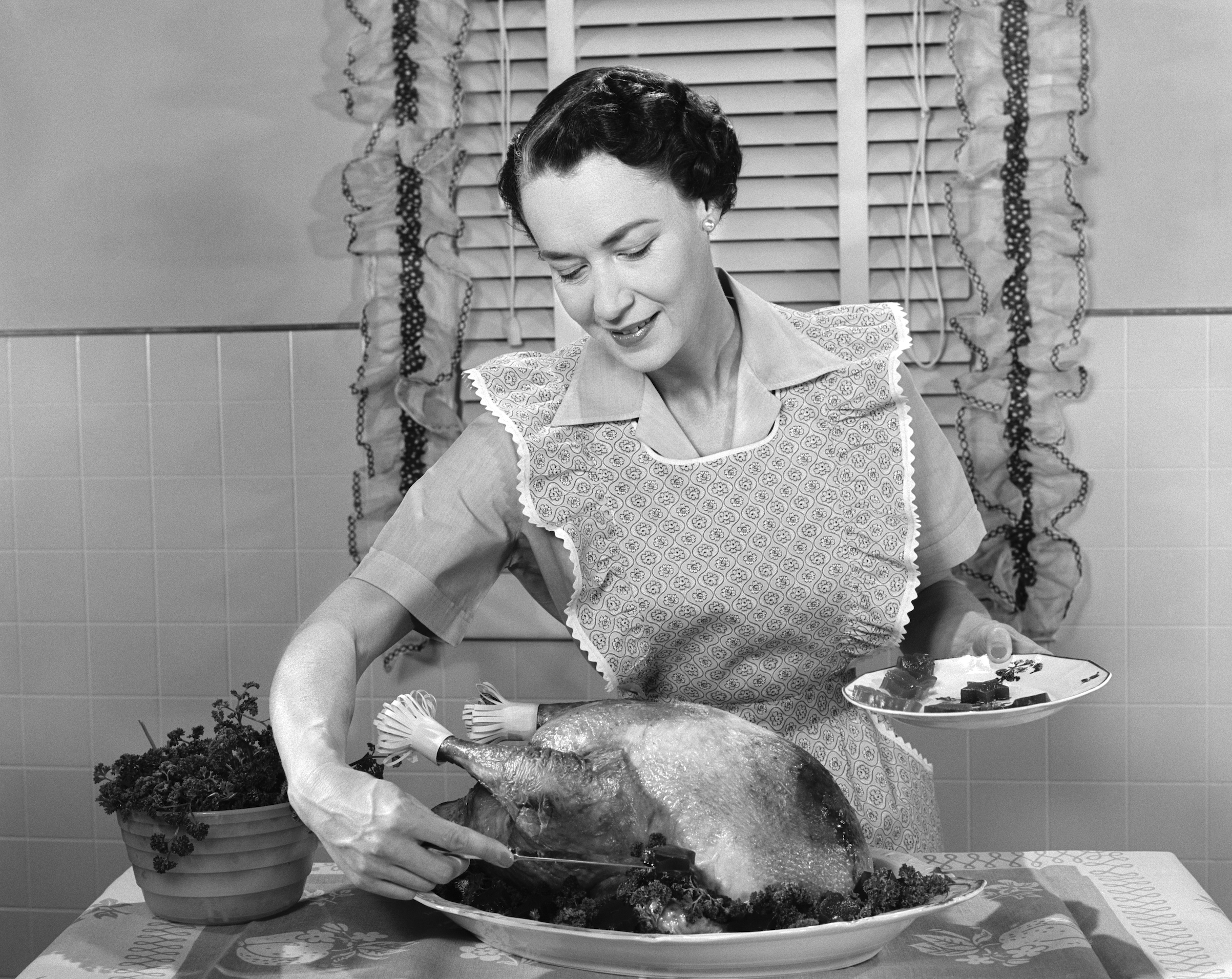 A woman dished cranberry sauce around a turkey in the 1950s