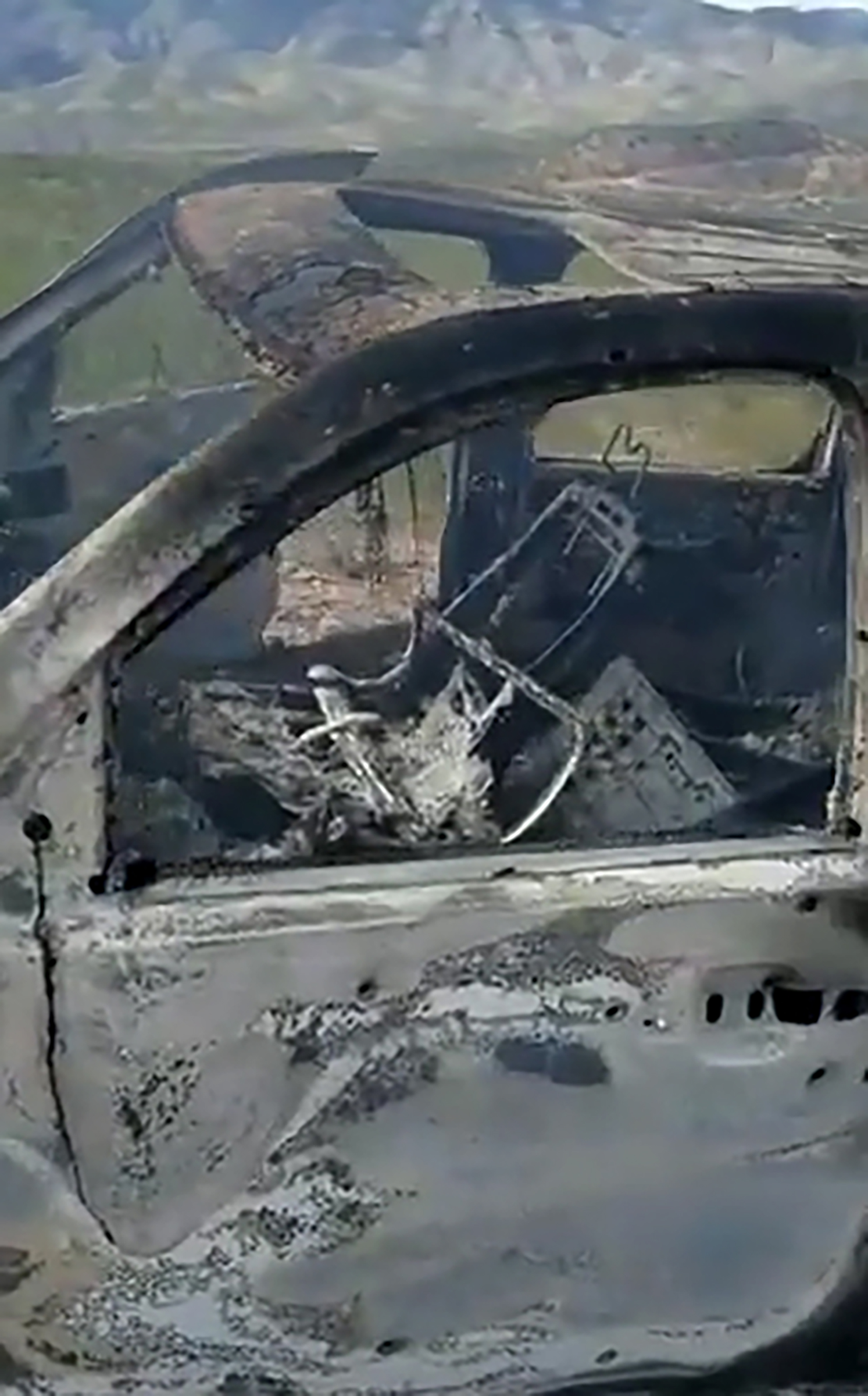 TV grab from a video published by Lebaron's family on social media showing a burnt vehicle that was carrying three women and six children from an American Mormon family near Rancho de la Mora, in the boundaries of Sonora and Chihuahua states, northern Mexico, on Nov. 4, 2019.