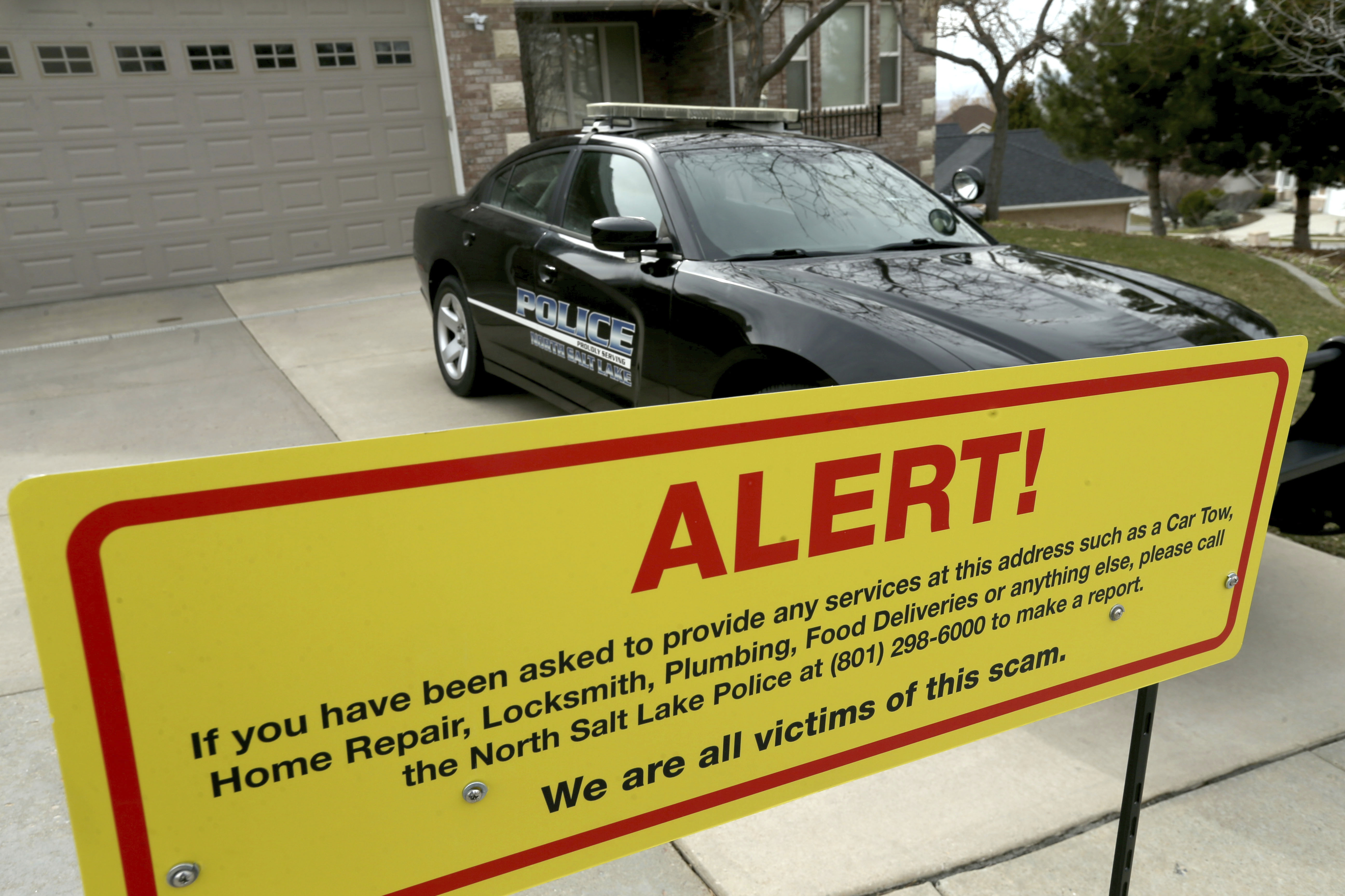 This photo shows a warning sign and a police officer's vehicle at Walt Gilmore's home in North Salt Lake, Utah on March 21, 2019.