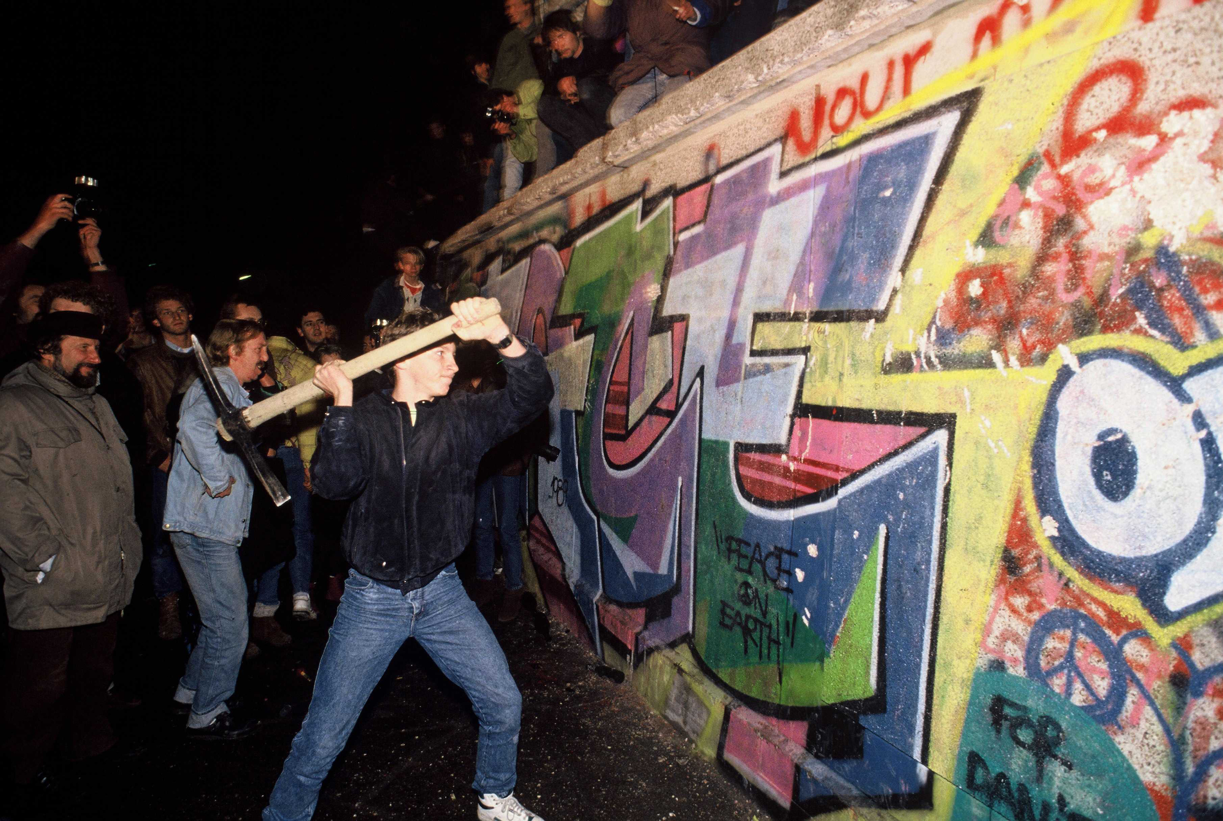 A man attacks the Berlin Wall with a pickaxe on the night of Nov. 9, 1989 as news spread rapidly that the East German Government would now start granting exit visas to anyone who wanted to go to the West.