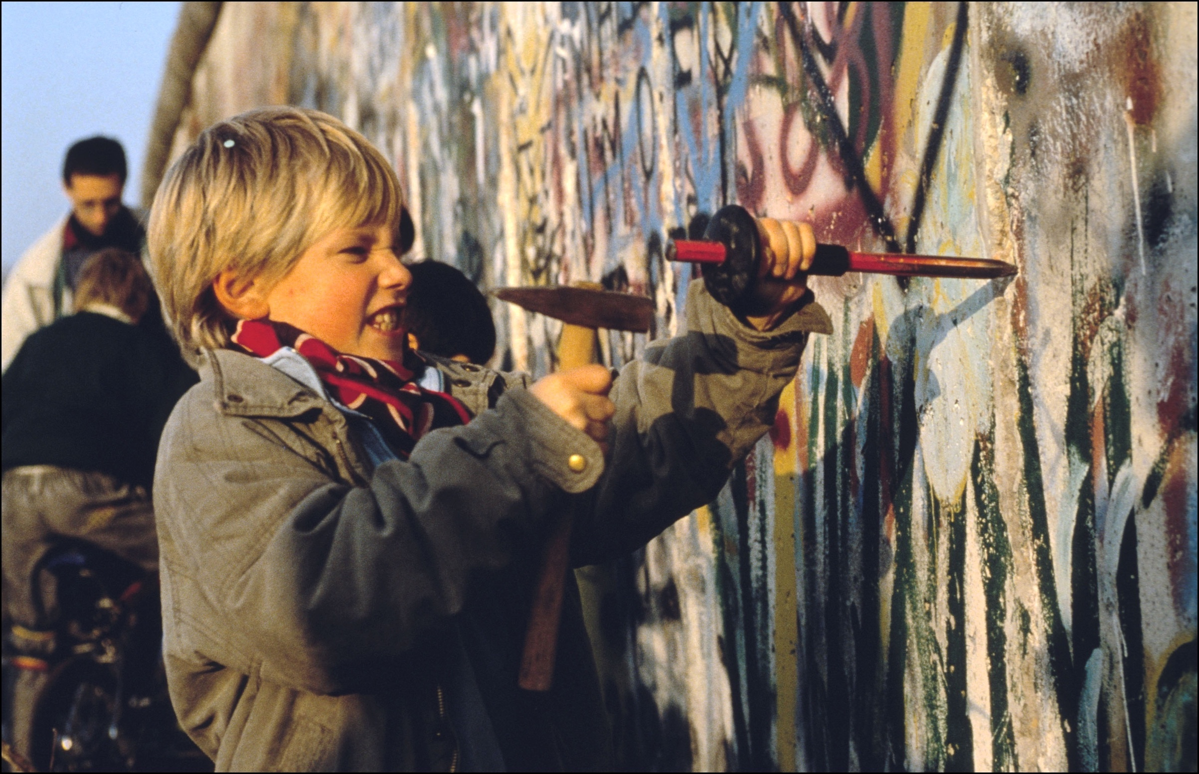 A boy chips at the Berlin Wall on Nov. 12, 1989, in Berlin.