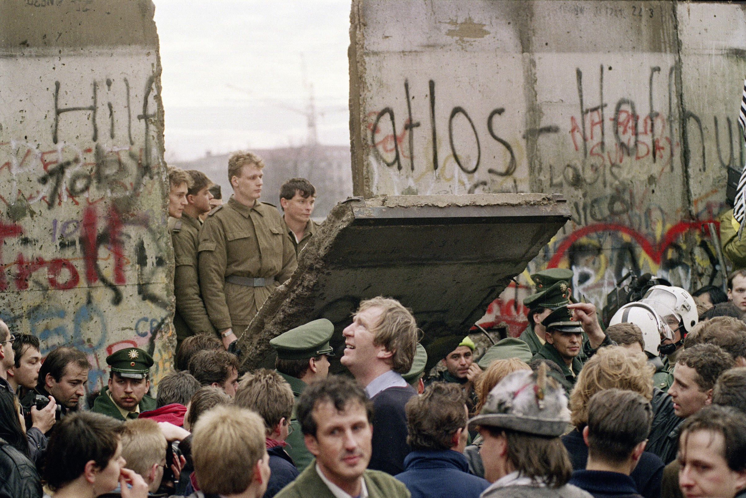 West Berliners crowd in front of the Berlin Wall early Nov. 11, 1989, as they watch East German border guards demolishing a section of the wall in order to open a new crossing point between East and West Berlin, near the Potsdamer Square.