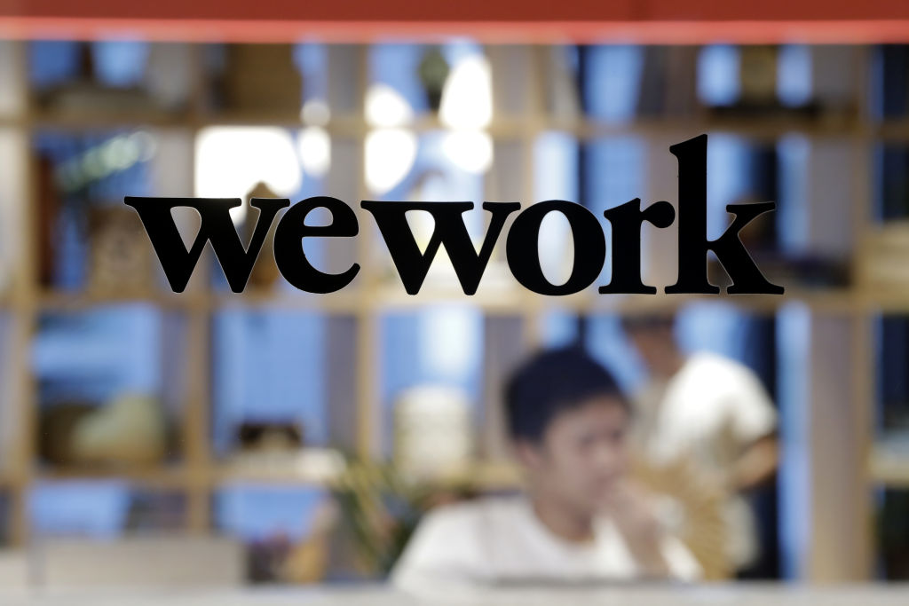 The WeWork logo sits on display on a glass door of the entrance to the WeWork Ocean Gate Minatomirai co-working office space, operated by The We Company, in Yokohama, Japan, on Friday, Oct. 11, 2019.