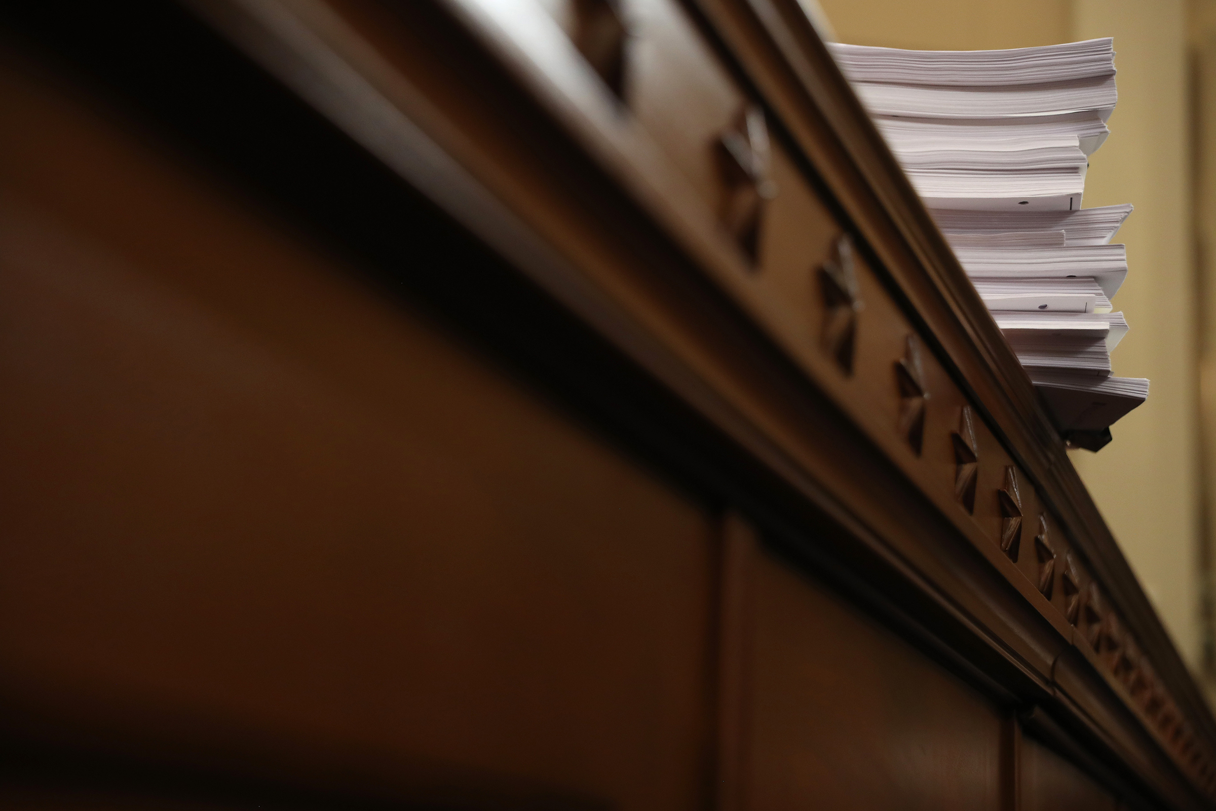 A stack of transcrips of depositions are shown during the third day of open hearings in the impeachment inquiry against President Donald Trump, Nov. 19, 2019.