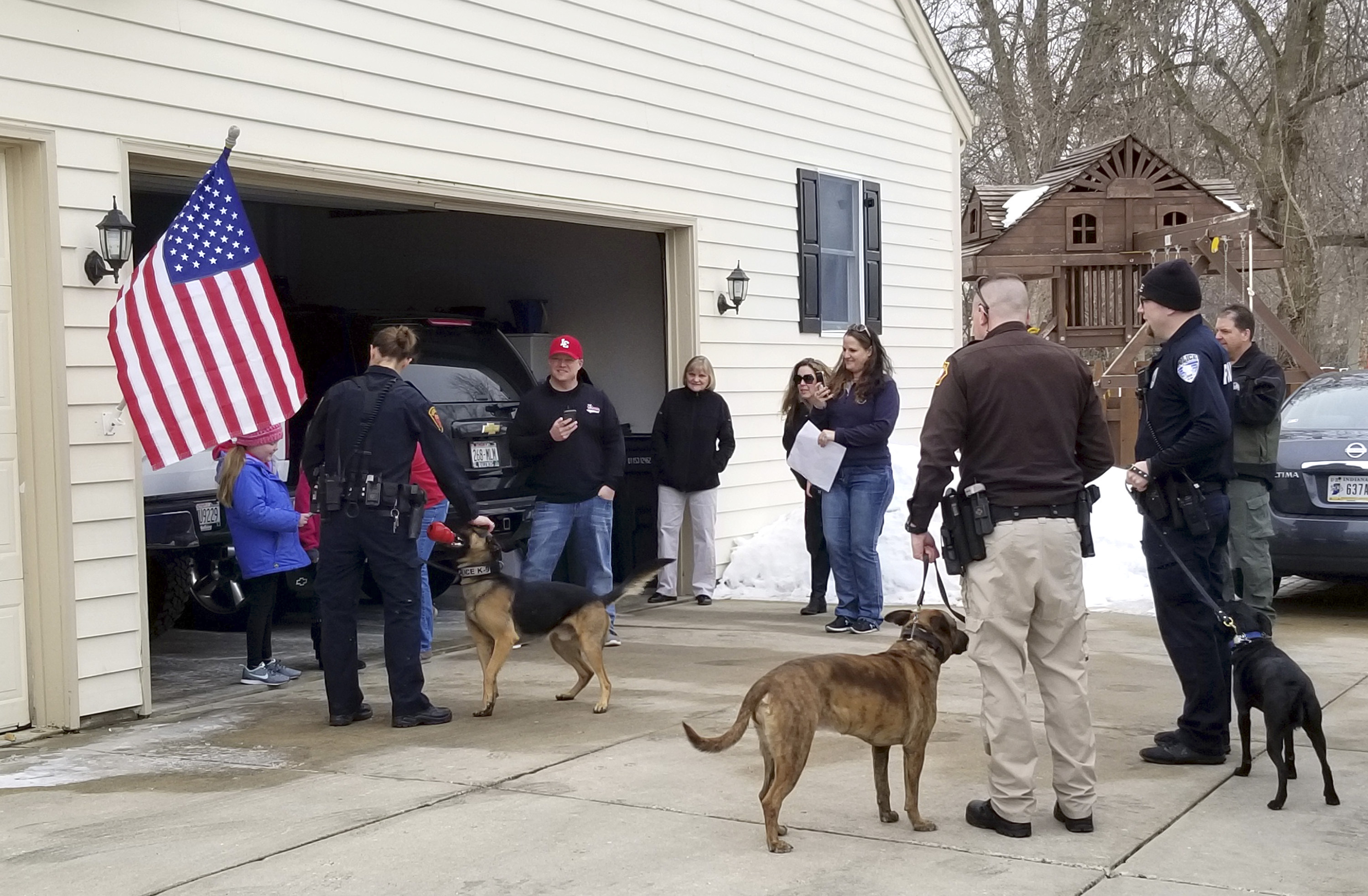 In this March 9, 2019 photo provided by the Hartford Police Department, Emma Mertens from Hartland, Wis., left, is visited by several K9 law enforcement officers and their dogs at her home in Hartford.