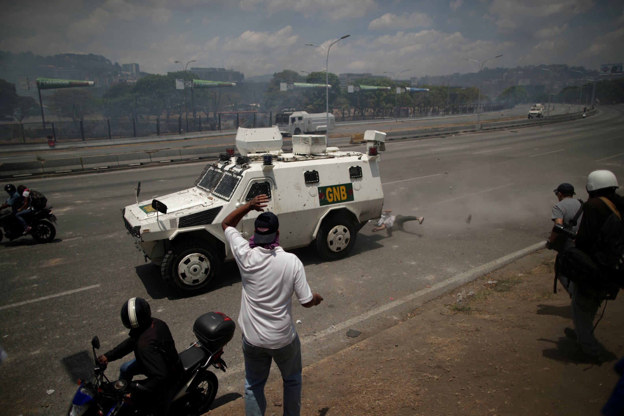 An opposition demonstrator is struck by a Venezuelan National Guard vehicle in Caracas on April 30. The protester survived the brush with death.