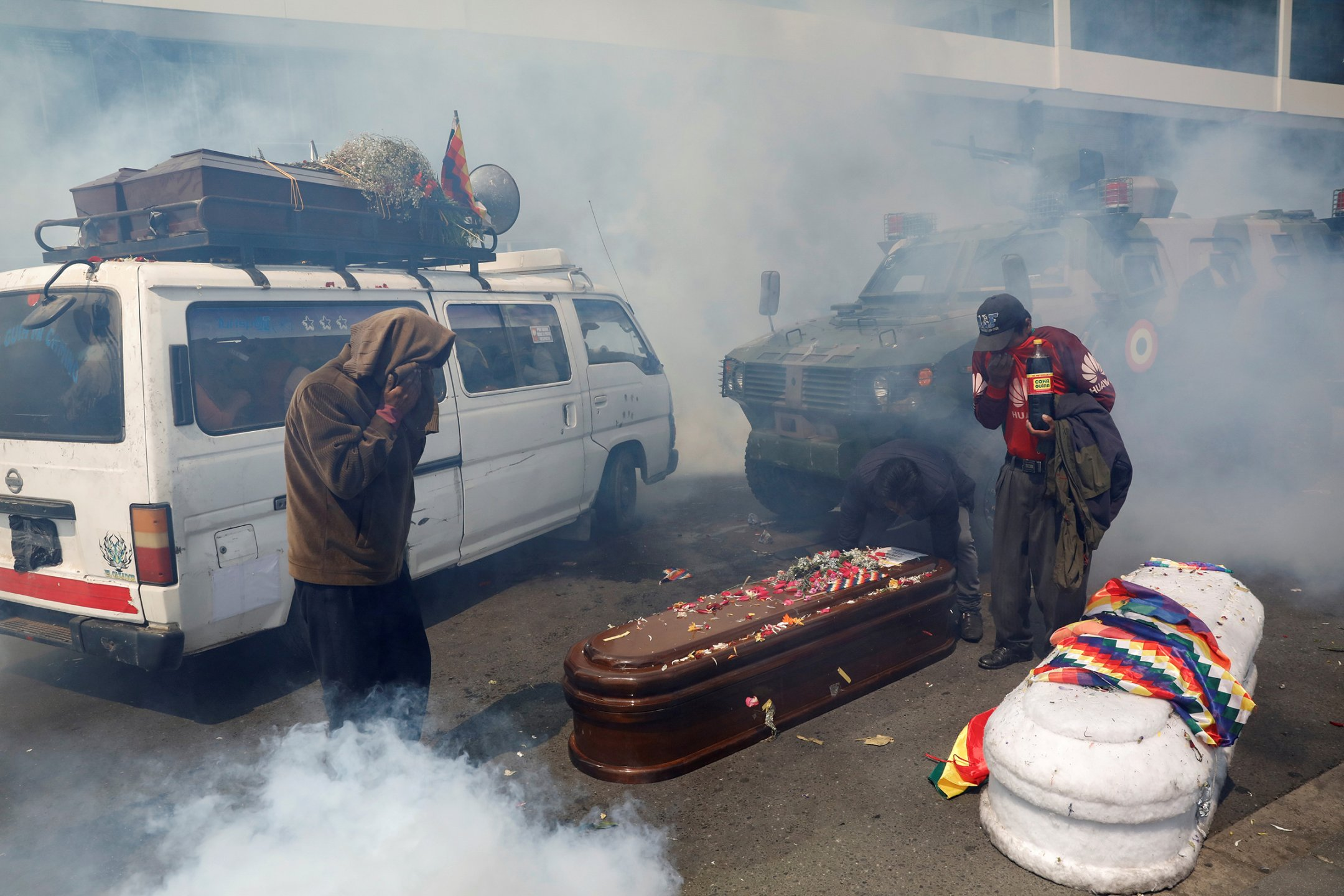Supporters of former Bolivian President Evo Morales take cover from tear gas during a protest in La Paz on Nov. 21. They were carrying coffins of people they say were killed during recent clashes with security forces.