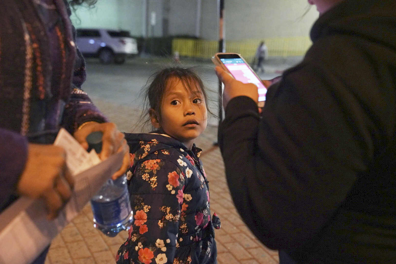 A 7-year-old asylum-seeker waits as her mother Isabel, right, and immigration lawyer Charlene D'Cruz, left, as they figure out where they will be spending the night after being processed at the Port of Entry in Brownsville, Texas, on Dec. 17, 2019.