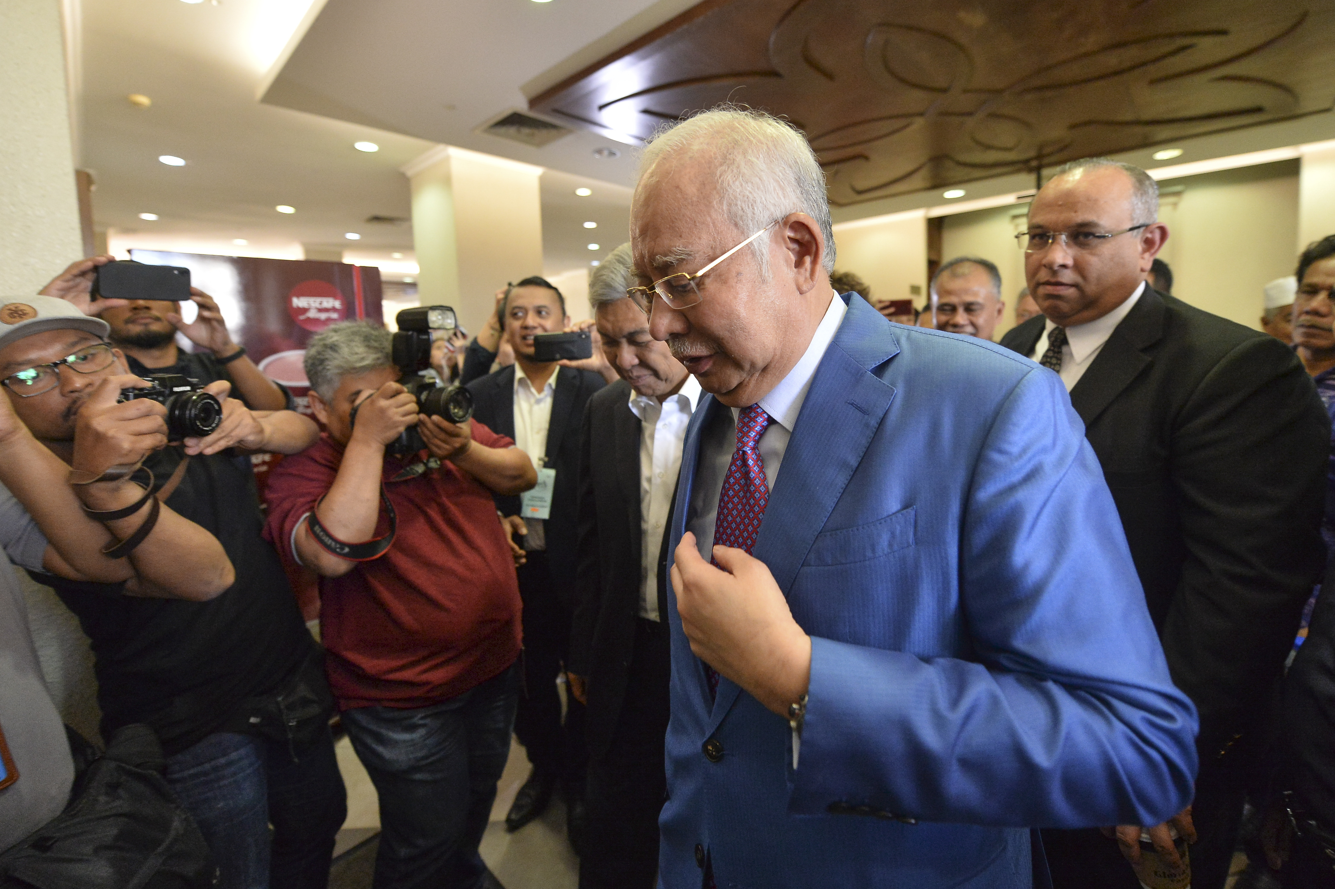 Former Malaysian Prime Minister Najib Razak, center, walks out from the courtroom at the court house in Kuala Lumpur, Malaysia for his corruption trial Tuesday, Dec. 3, 2019.