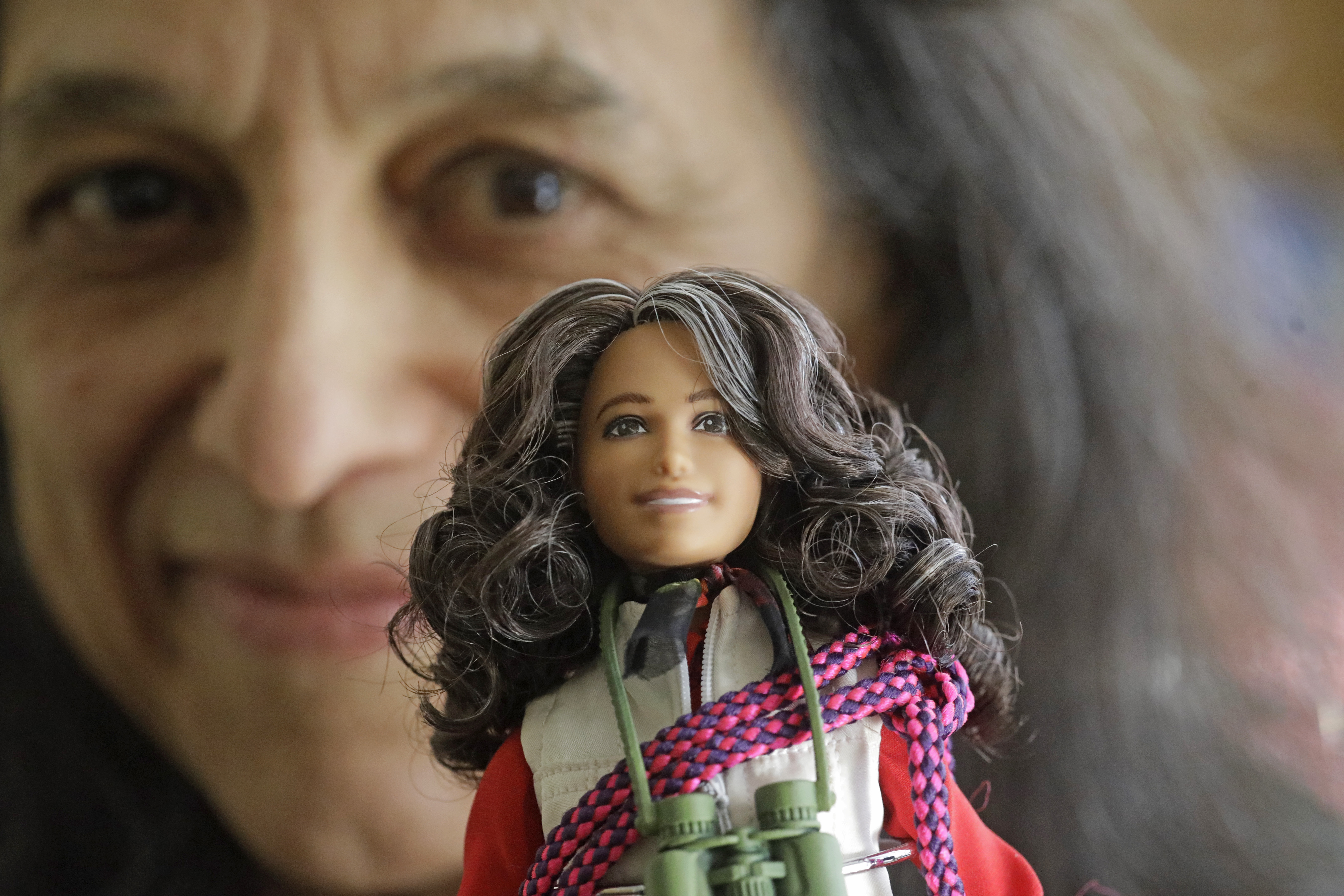 In this Dec. 3, 2019, photo, ecologist Nalini Nadkarni is shown in her lab on the University of Utah campus in Salt Lake City holding a Barbie created to look like her when she's climbing into the treetops to study the rainforest canopy.
