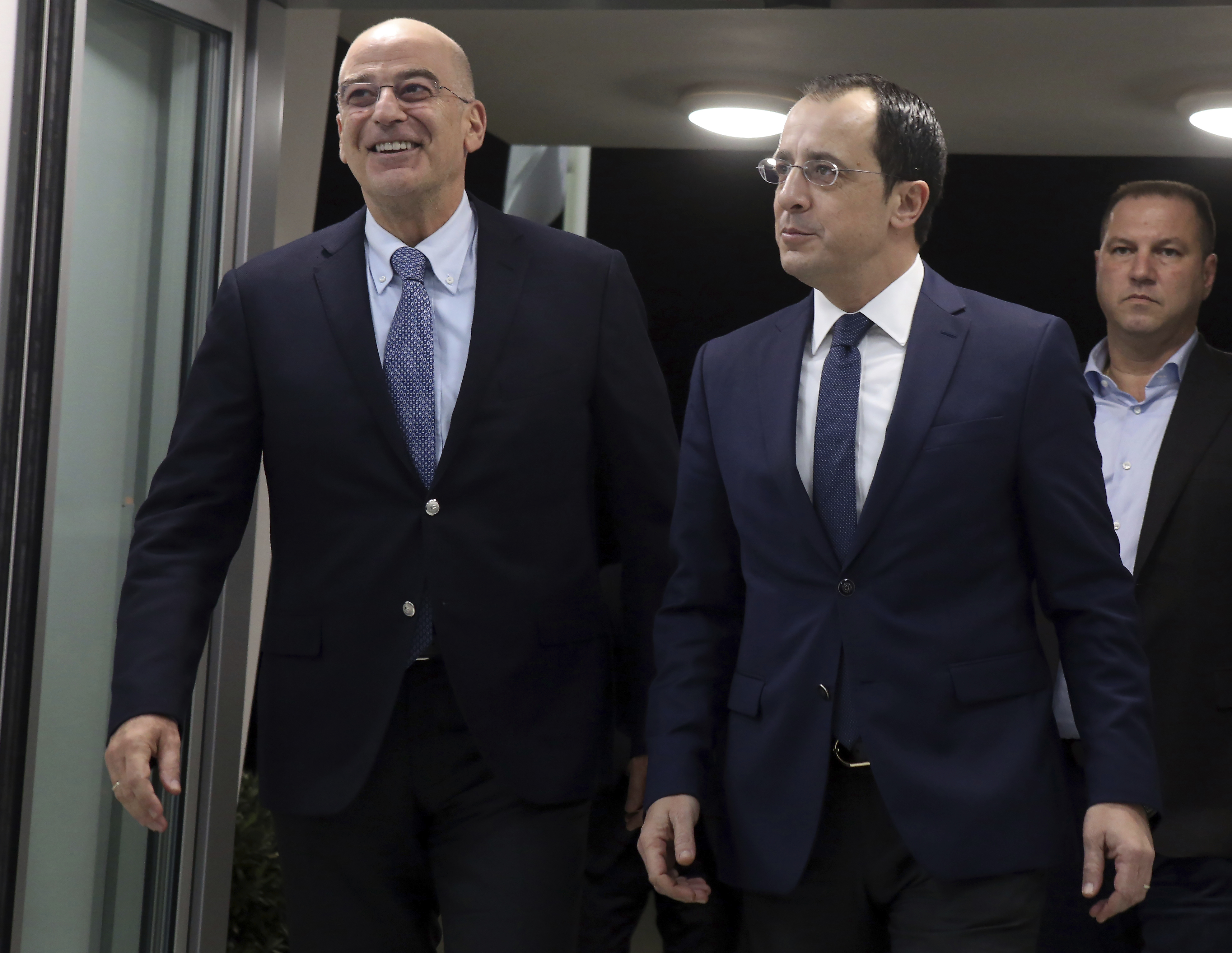 Greece's Foreign Minister Nikos Dendias, left, talks with Cypriot counterpart Nikos Christodoulides before their meeting at Cyprus' main airport in the coastal town of Larnaca on Sunday, December 22, 2019.