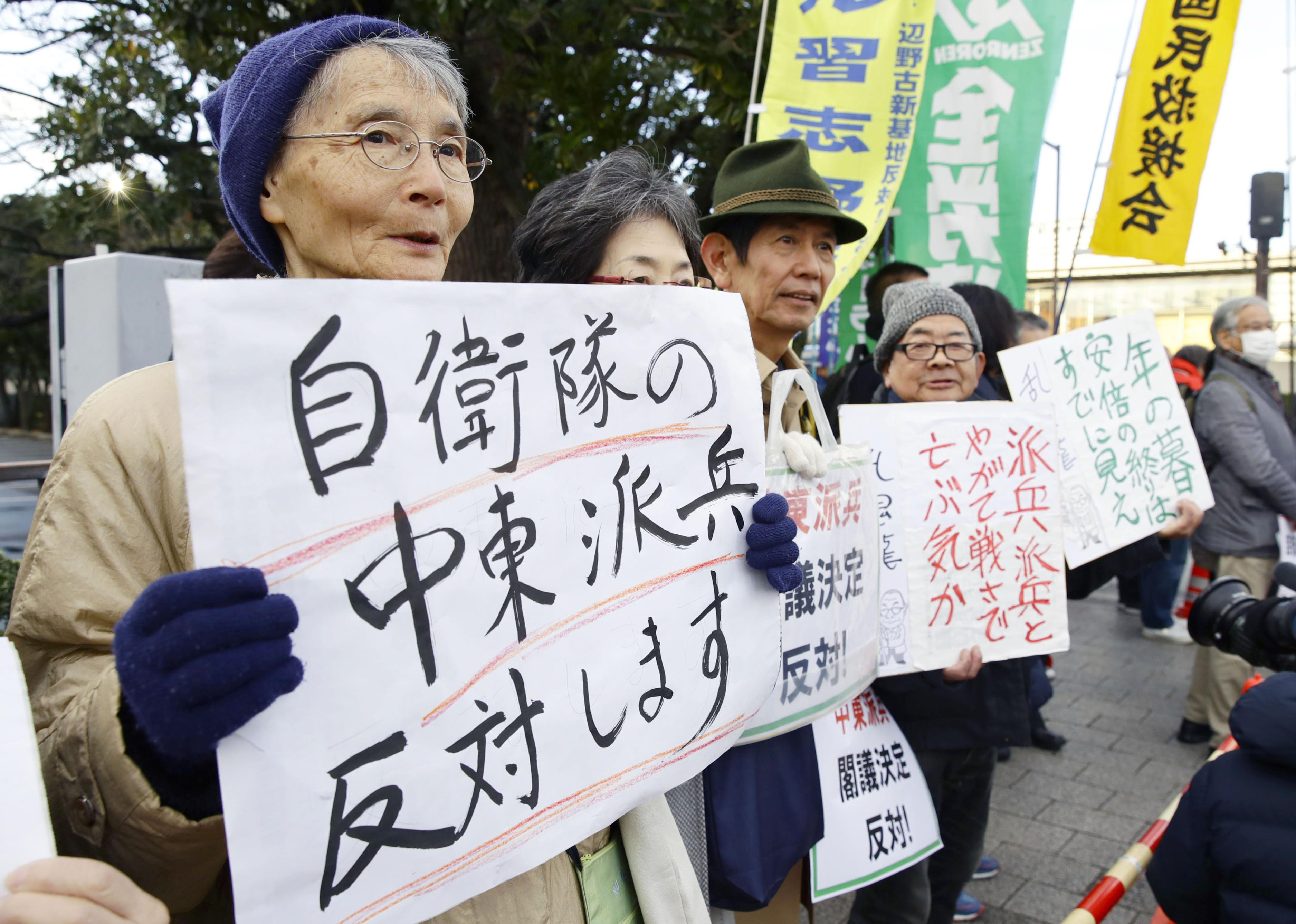 People hold placards protesting against a troop dispatch to Middle East outside the prime minister's official residence in Tokyo Friday, Dec. 27, 2019.