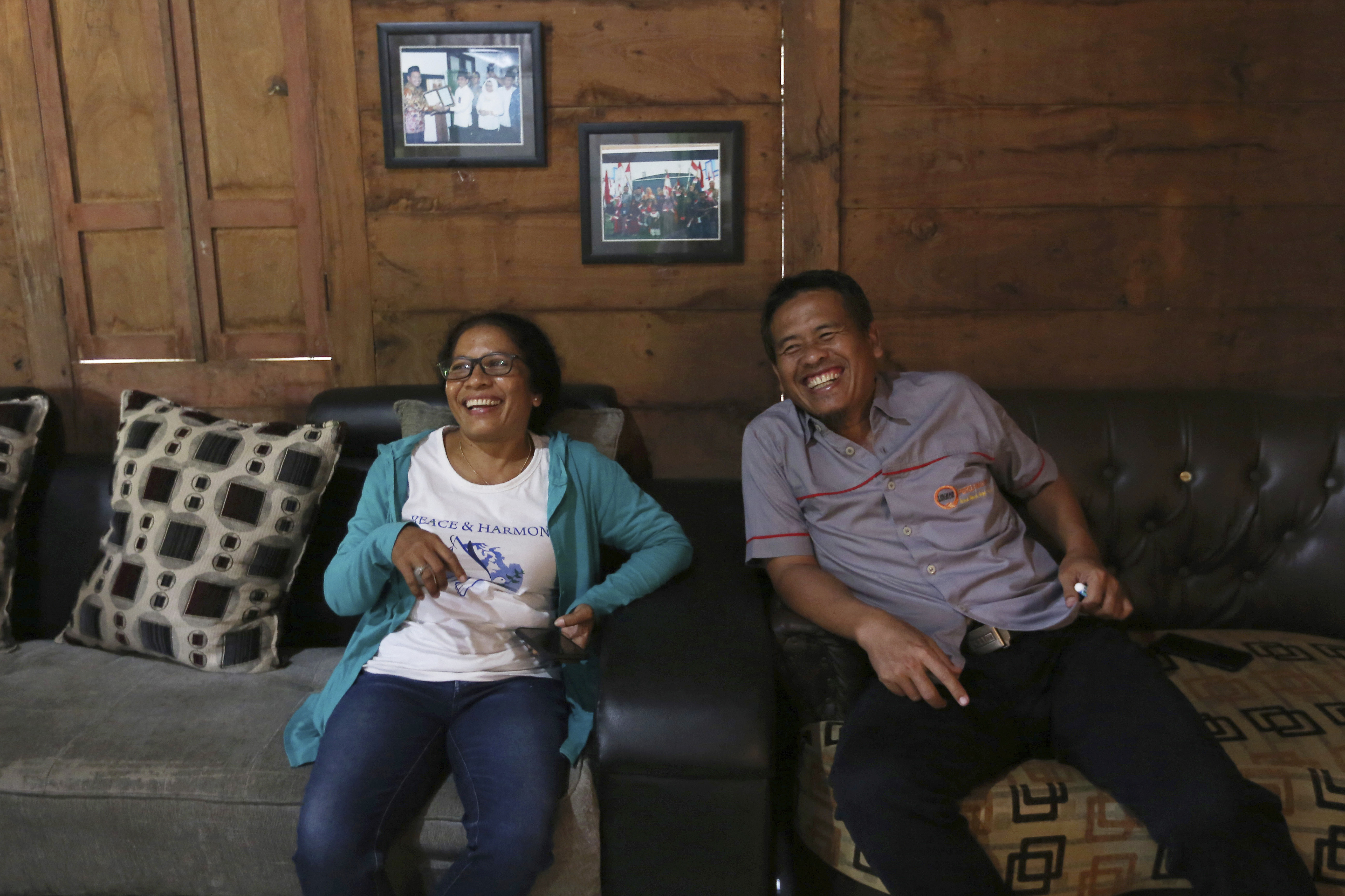 Ni Luh Erniati, left, laughs with Ali Fauzi during her visit to Fauzi's house in Tenggulun, East Java, Indonesia, on Saturday, April 27, 2019. Erniati, whose husband was killed in the 2002 Bali bombings, and Fauzi, a former bombmaker whose brothers helped orchestrate the Bali attack, have reconciled as part of a peacebuilding program bringing together ex-terrorists and victims.