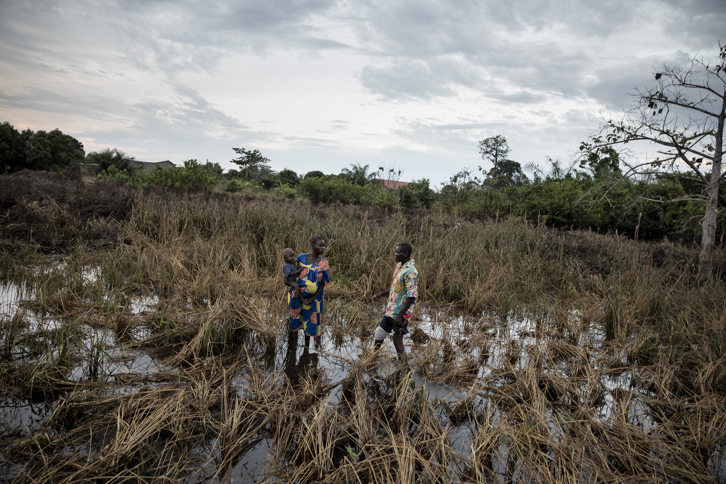 A neighbor and Locadie Lapenda, a 30-year old mother of four stand in her flooded rice field on Nov. 24, 2019.