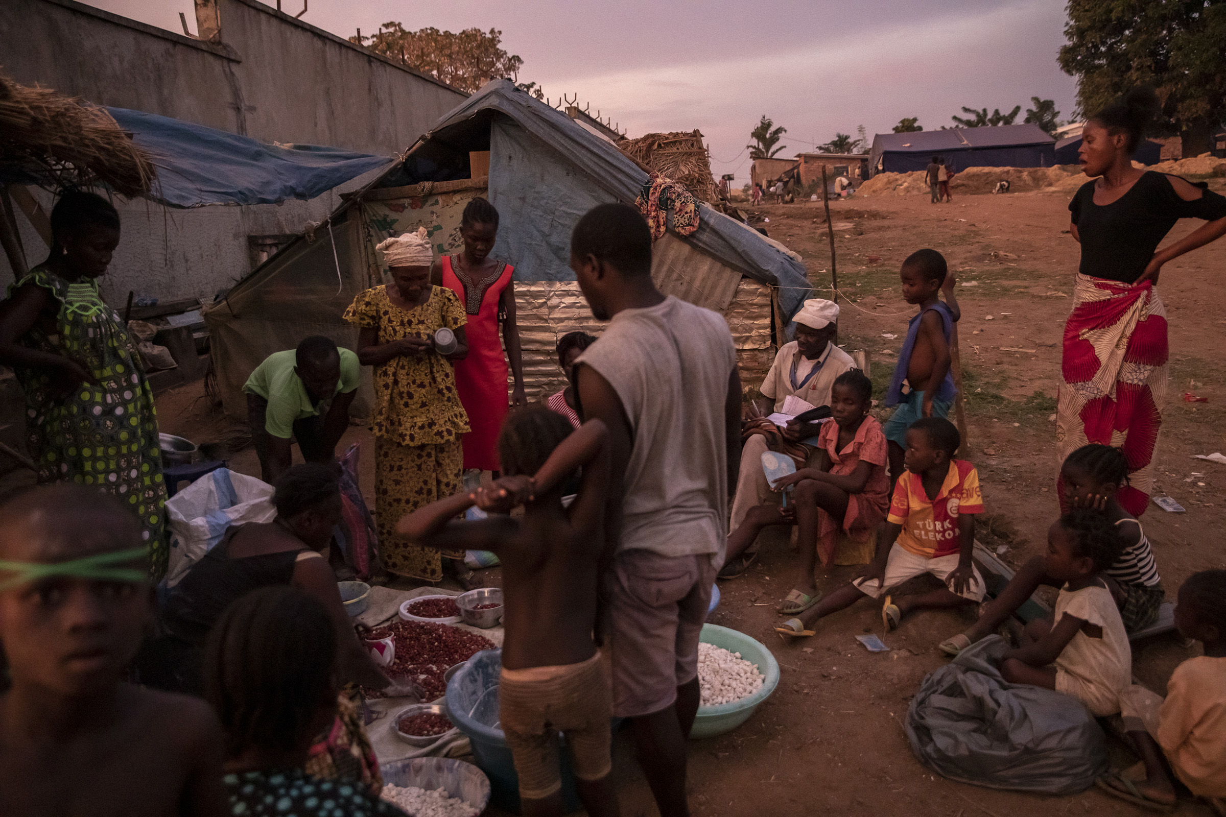 As the sun goes down, Guy Zegue distributes manioc in front of his shelter at the Socada camp on Nov. 23, 2019. The former member of the Central African army fled with his wife and children as all of Monkey Island was flooded.