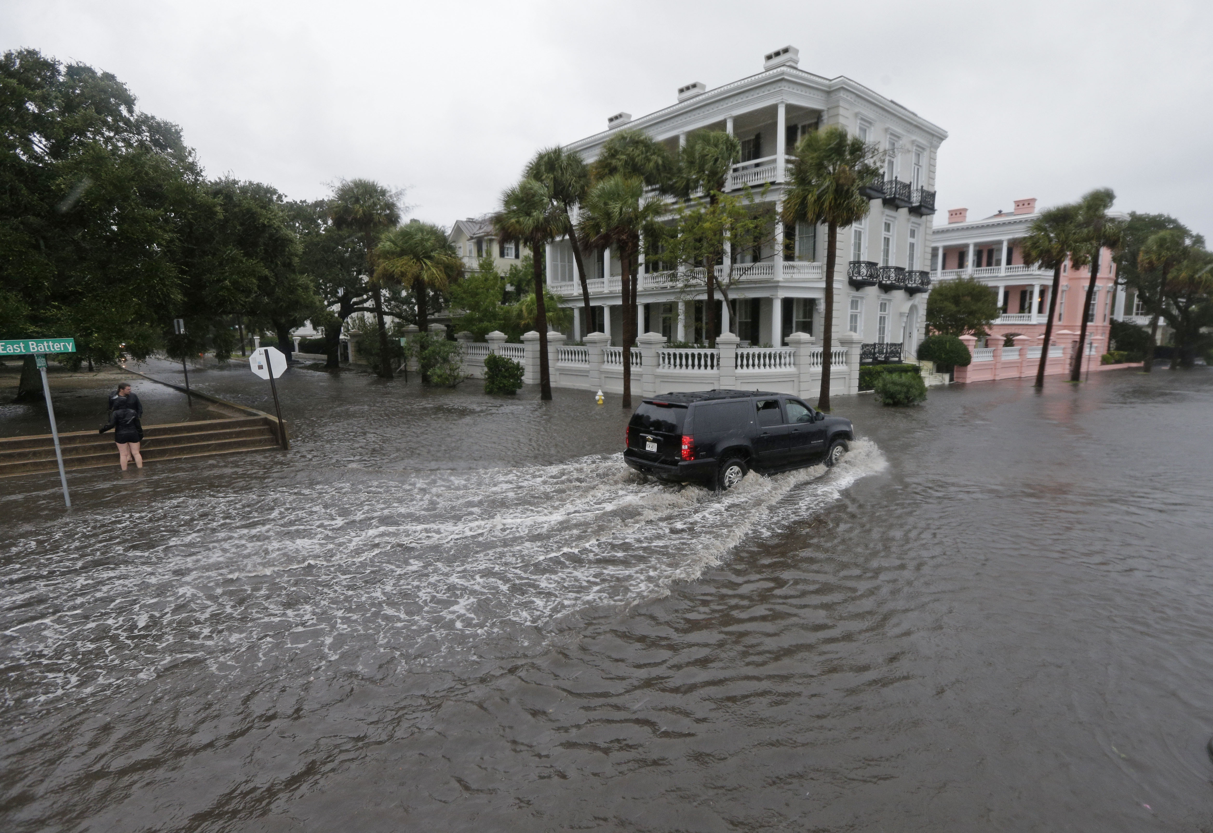 In this Oct. 3, 2015, file photo, a driver takes his truck through a flooded street in Charleston, S.C. Historic coastal cities in the Southeast U.S. have survived disease outbreaks, wars and hurricanes over the past three centuries. Now they are trying to figure how to survive rising seas from climate change.