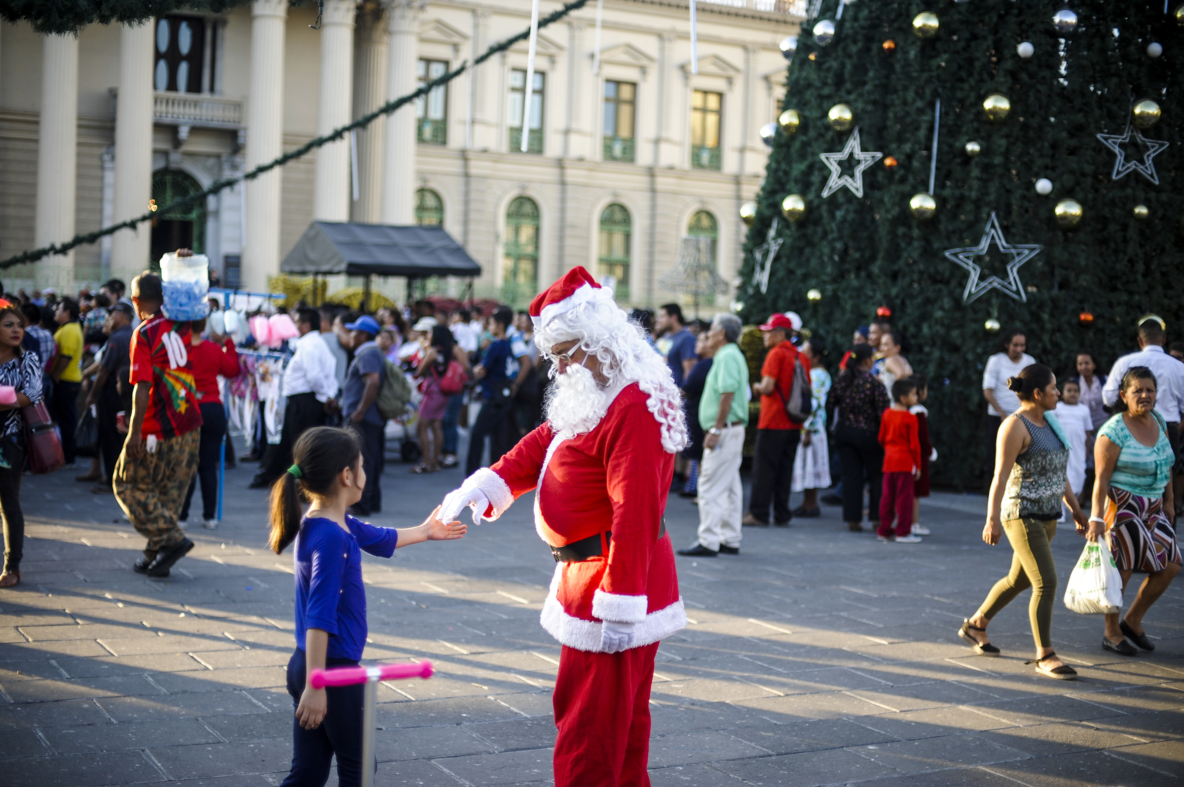 A man dressed up as a Santa Claus greets a girl during Christmas season on Dec. 15, 2019 in San Salvador, El Salvador.