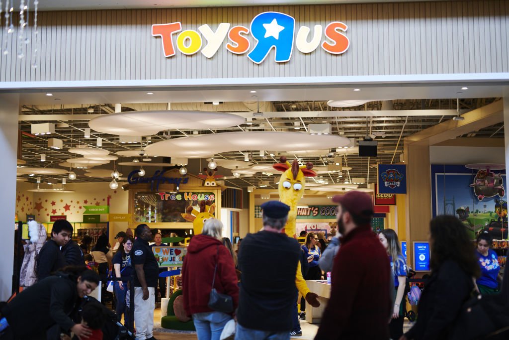 Shoppers pass in front of a Toys 'R' Us Inc. store at the Westfield Garden State Plaza mall on Black Friday in Paramus, N.J., on Nov. 29, 2019.