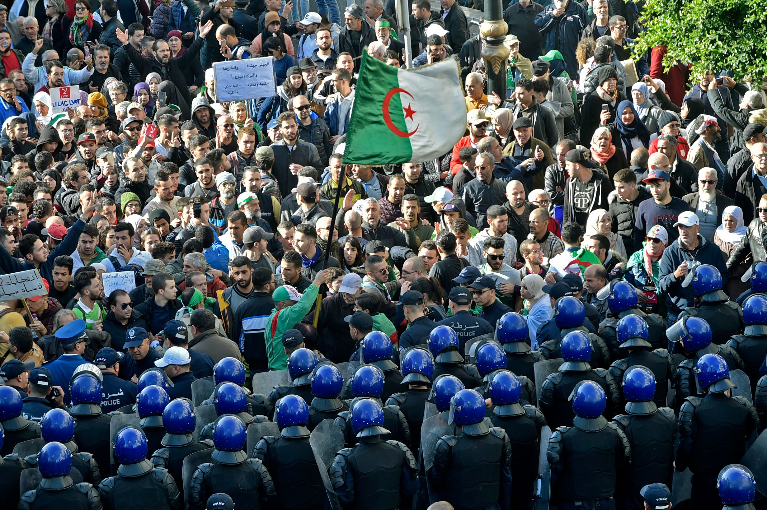 Algerian security surround protesters during an anti-government demonstration in the capital Algiers on December 11, 2019, ahead of the presidential vote scheduled for December 12. vote.