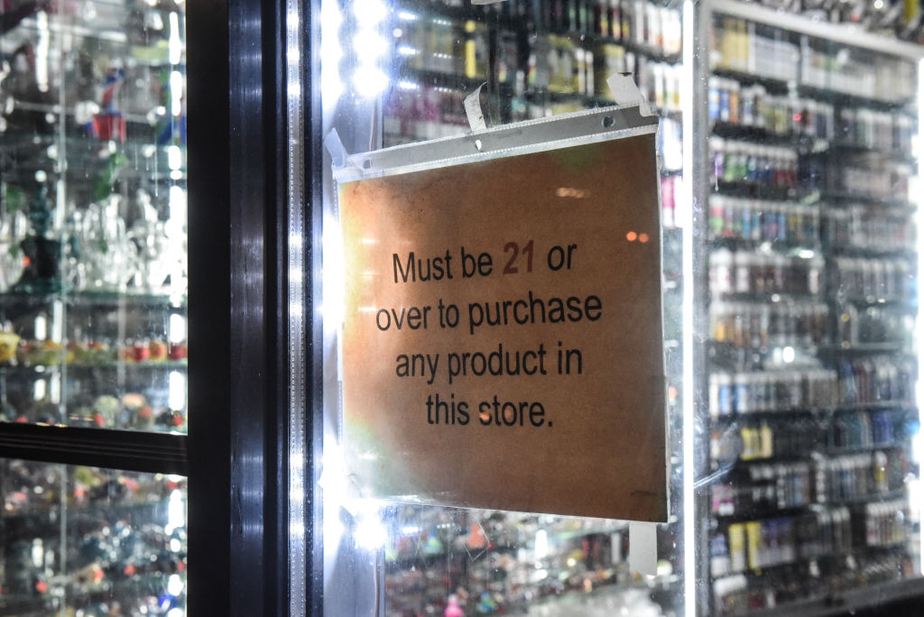 A sign that states  must be over 21  hangs in the store window of a  vape shop on Dec. 19, 2019 in New York City.