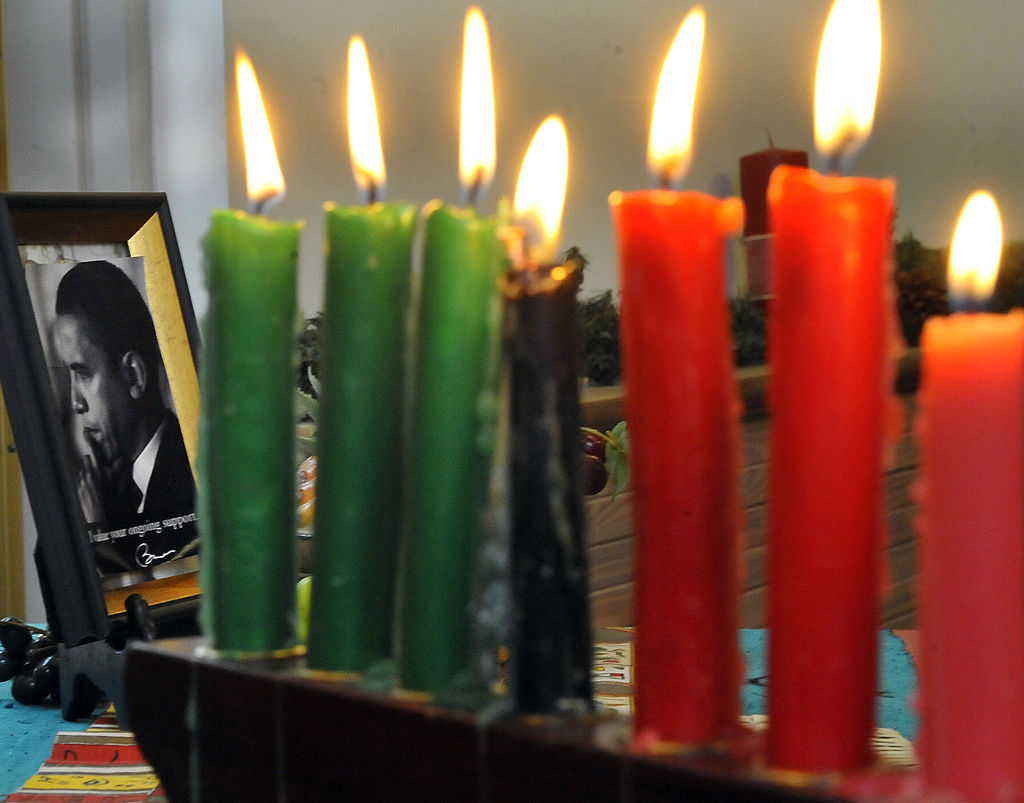 A photograph of President Obama beside lit candles during the Kwanzaa celebration at the Benjamin Banneker Historical Park and Museum on Saturday,  December 29, 2012 in Catonsville, Md.