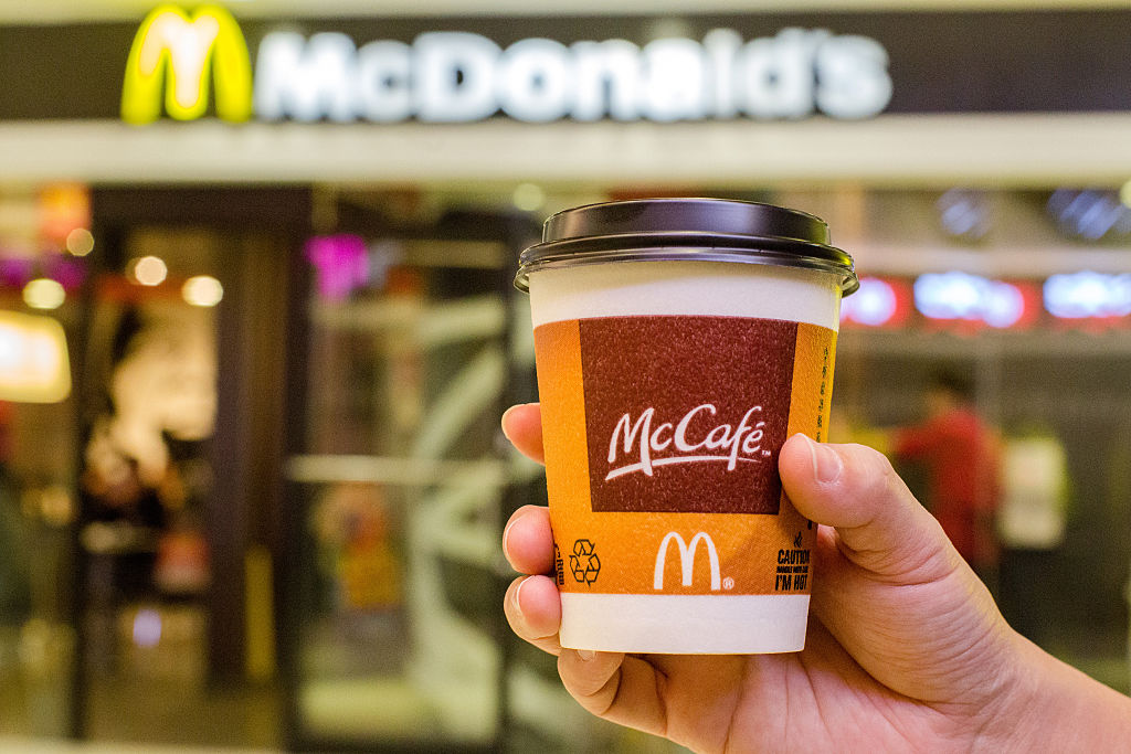 A customer holds a cup of Coffee served by McCafe out of a McDonald's restaurant.