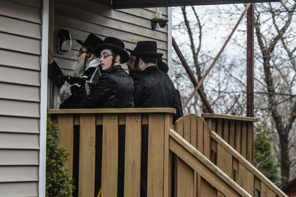 Rabbi Chaim Rottenberg (L) enters the backdoor of his house on Dec. 29, 2019 in Monsey, New York. Five people were injured in a knife attack during a Hanukkah party and a suspect was later arrested in Harlem.