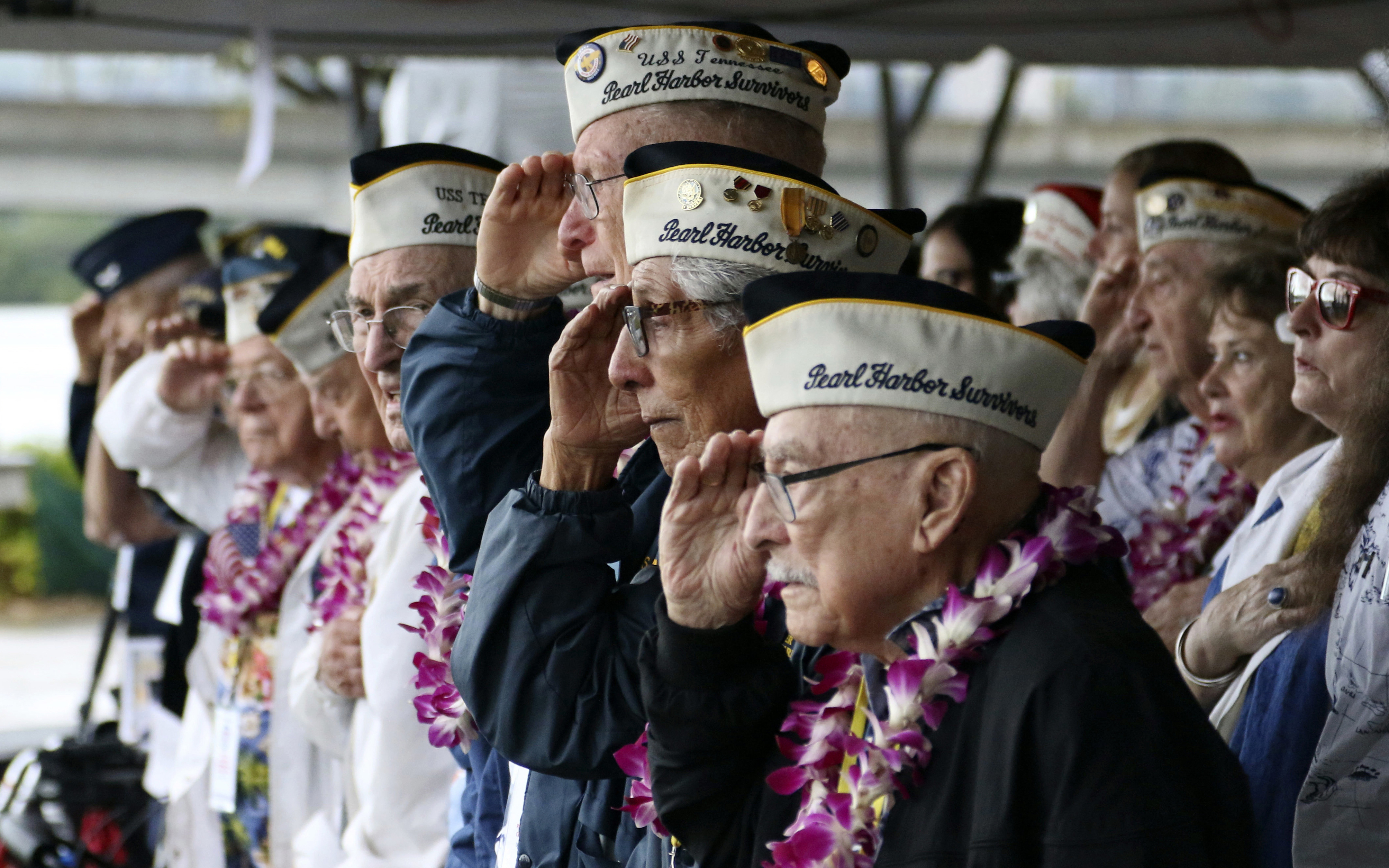 In this Dec. 7, 2018, file photo, Pearl Harbor survivors salute during the National Anthem at a ceremony in Pearl Harbor, Hawaii marking the 77th anniversary of the Japanese attack. Survivors and members of the public are expected to gather in Pearl Harbor on Saturday, Dec. 7, 2019, to remember those killed when Japanese planes bombed the Hawaii naval base 78 years ago and launched the U.S. into World War II. Organizers plan for about a dozen survivors of the attack to attend the annual ceremony, the youngest of whom are now in their late 90s.