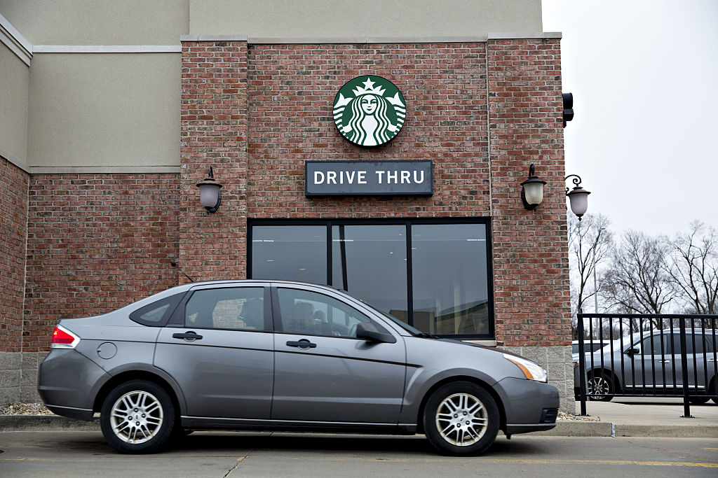 A vehicle stands at the drive thru of a Starbucks Corp. coffee shop in Peoria, Illinois, on Wednesday, Jan. 25, 2017.