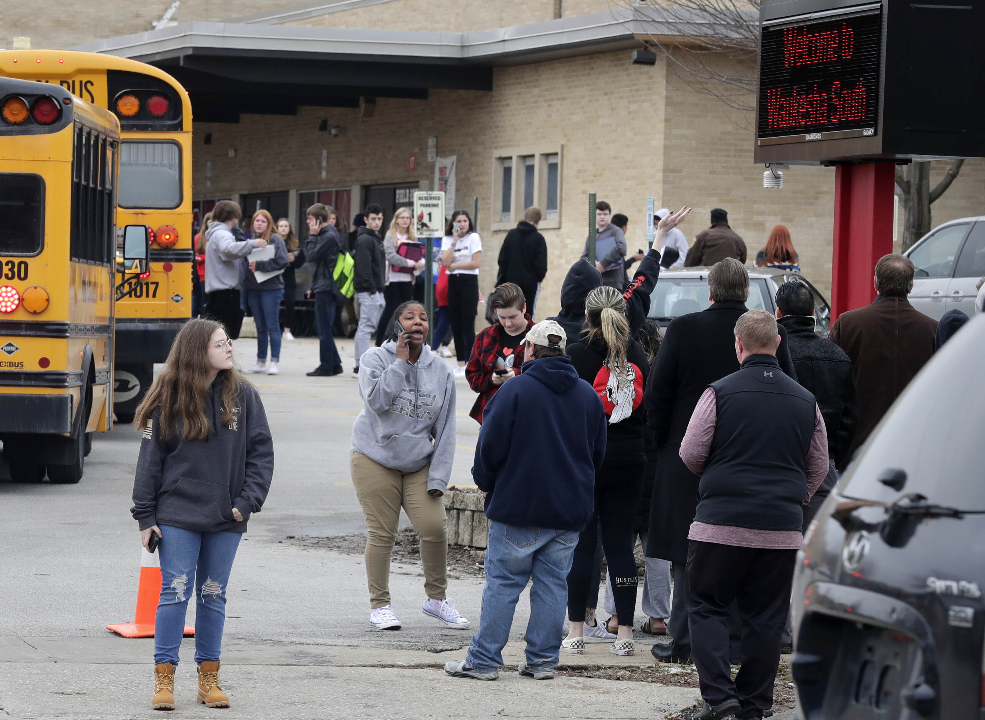 Waukesha South High School students find their waiting parents and friends and hug after evacuated the building after police shot an armed student in a classroom on Monday, Dec. 2, 2019.