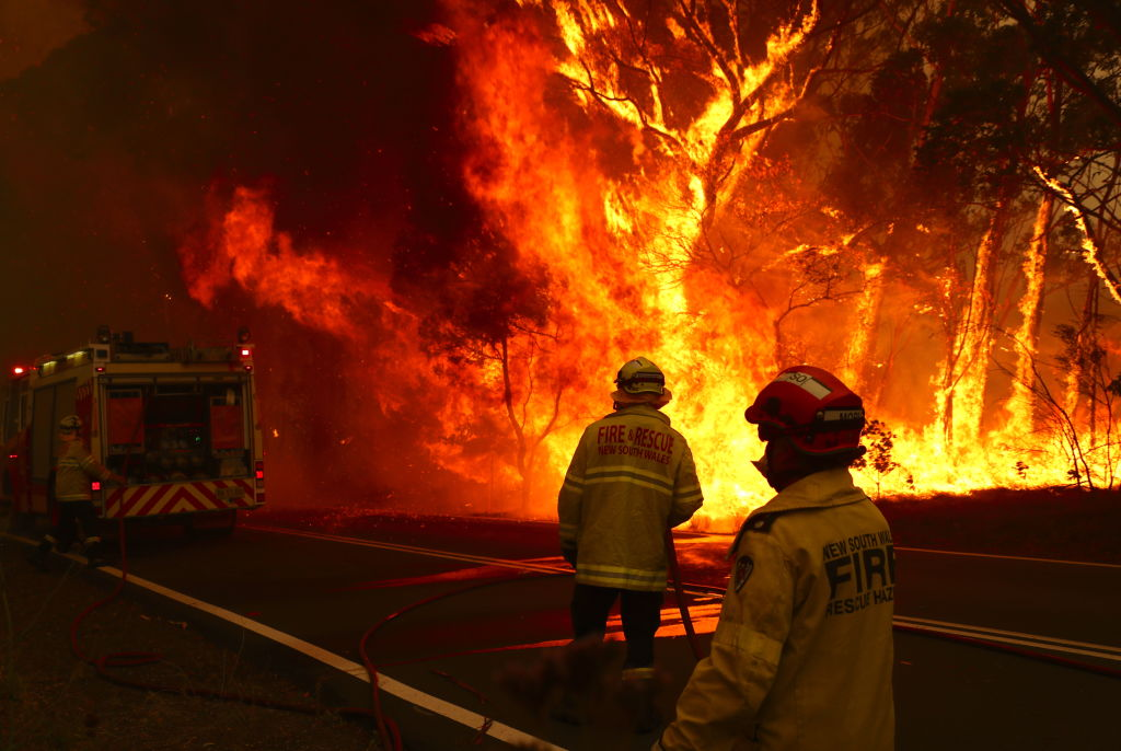 Fire and Rescue personal run to move their truck as a bushfire burns next to a major road and homes on the outskirts of the town of Bilpin outside of Sydney, Australia on Dec. 19, 2019.