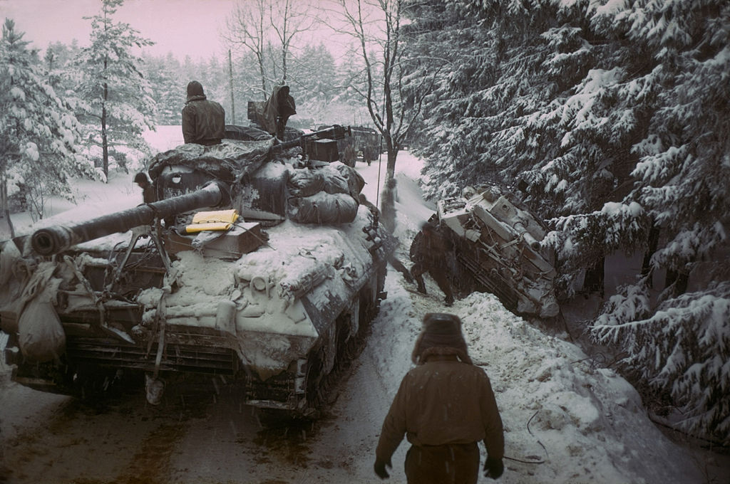 An American tank moves past another gun carriage which slid off icy road in the Ardennes Forest on Dec. 20, 1944.
