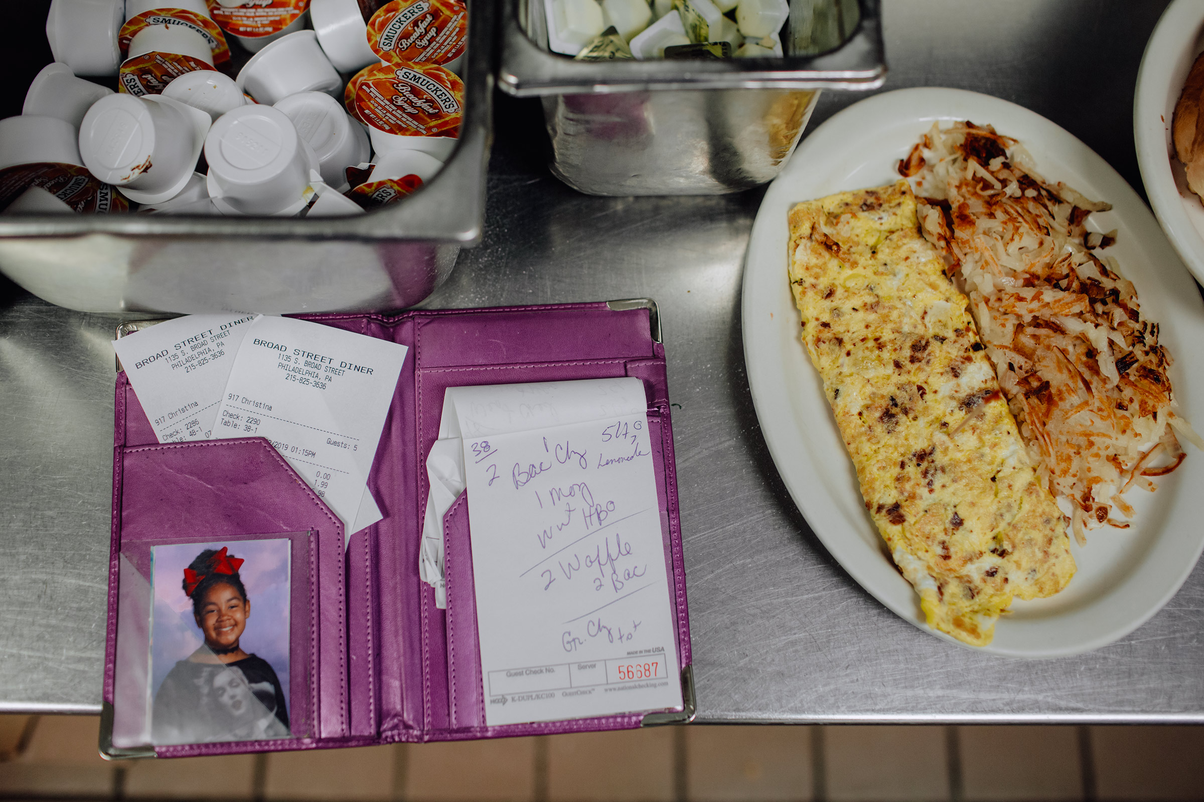 In the kitchen at the Broad Street Diner in Philadelphia, waitress Christina Munce keeps her daughter's photo next to her pad for taking orders. Sept. 2 issue.