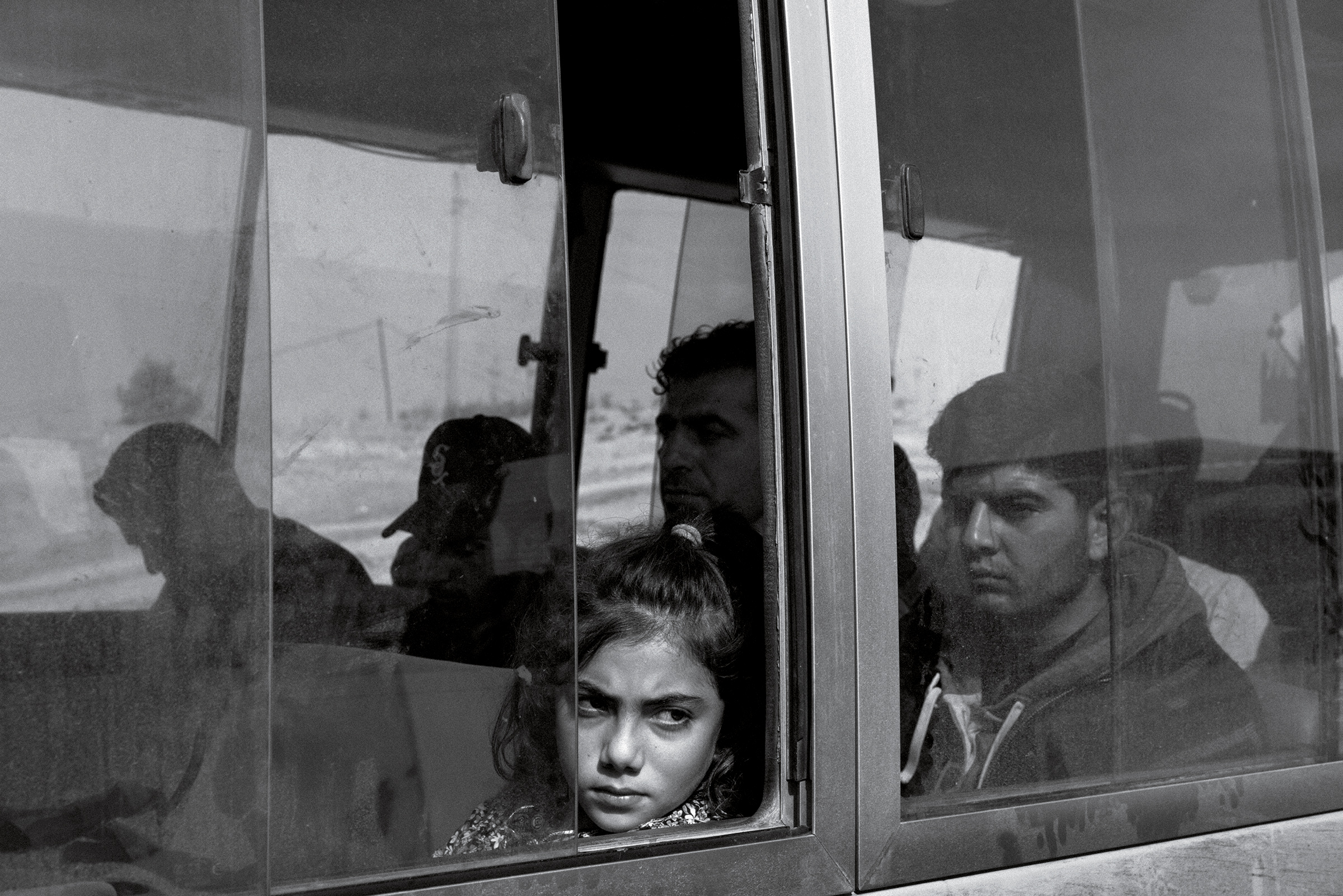 Nuhat Abdul Hamid, 9, from the Syrian Kurdish town of Darbasiyah, aboard a bus transporting refugees to the Bardarash camp in Iraq on Nov. 1. Nov. 25 issue.