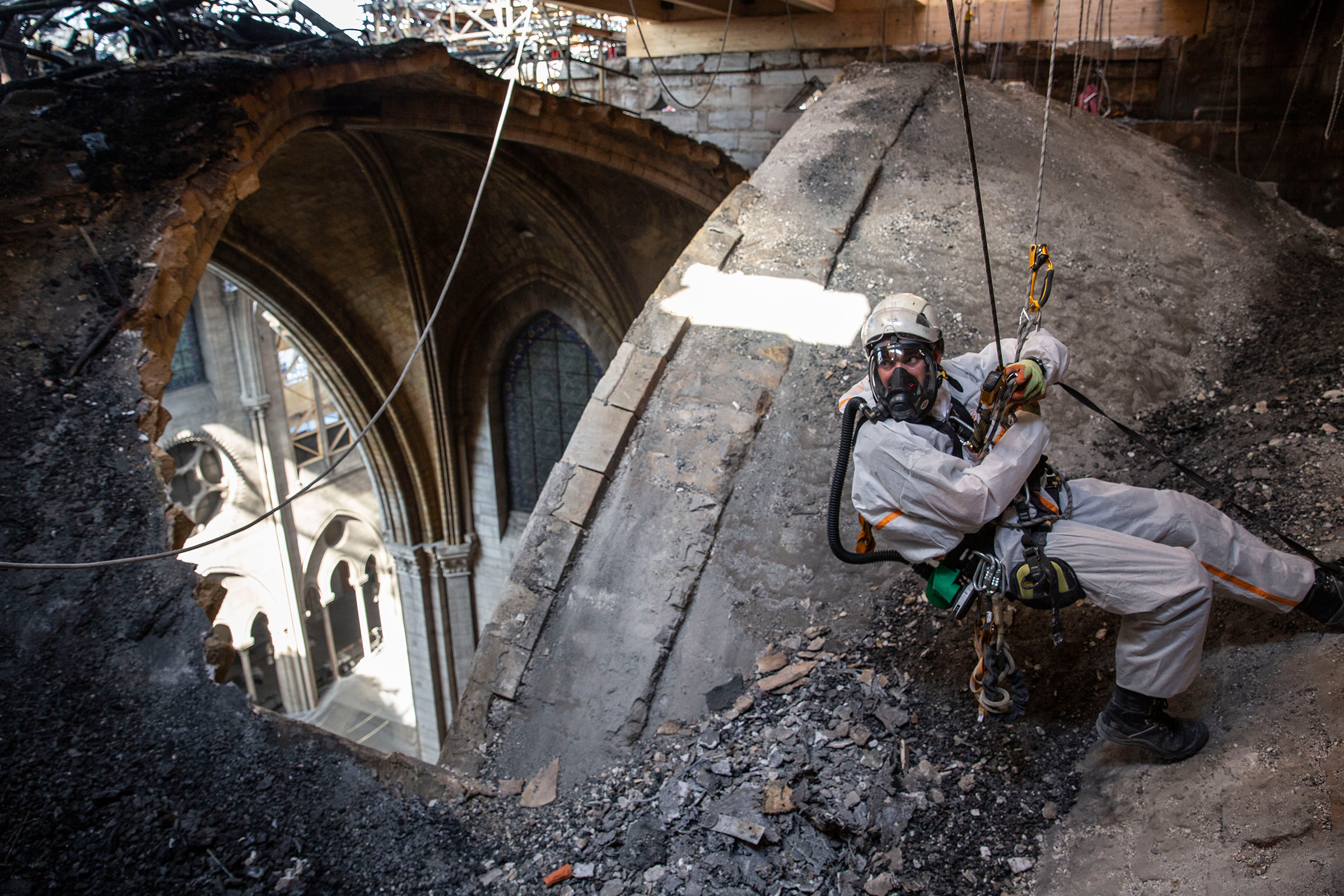 A technician near an open part of Notre Dame's roof in Paris on June 25. After the April fire, some sections of the cathedral have since been exposed to rainfall and high temperatures that France has experienced. Aug. 5 issue.